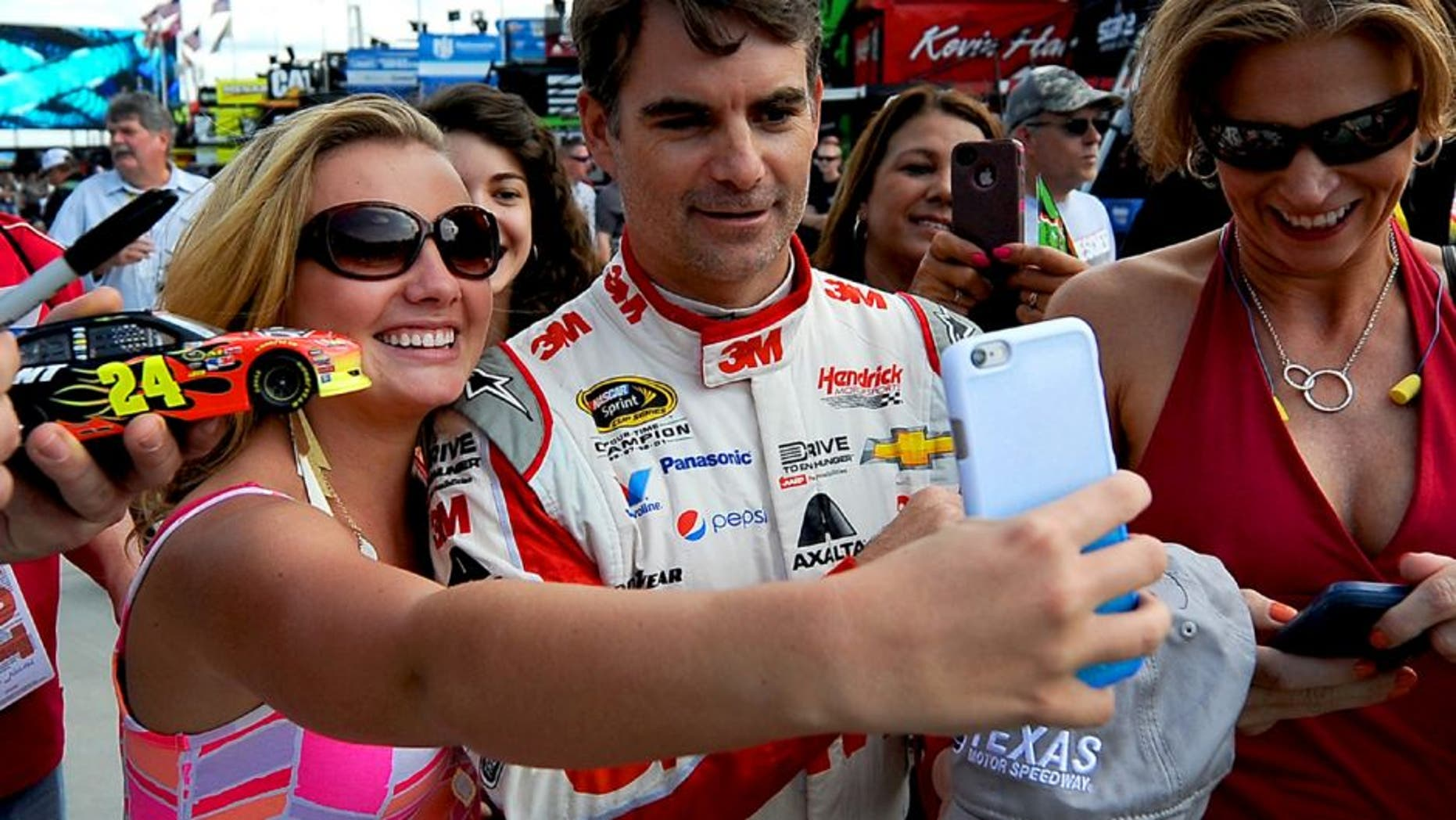 NASCAR fan Savannah Dean, left, of Akron, Ohio, smiles as she takes a selfie with NASCAR Sprint Cup Series driver Jeff Gordon, right, as he walks to his car at at Charlotte Motor Speedway in Concord, N.C., on Friday, Oct. 9, 2015. Saturday's Bank of America 500 will be Gordon's final start in a Cup Series race at Charlotte Motor Speedway. (Jeff Siner/Charlotte Observer/TNS via Getty Images)