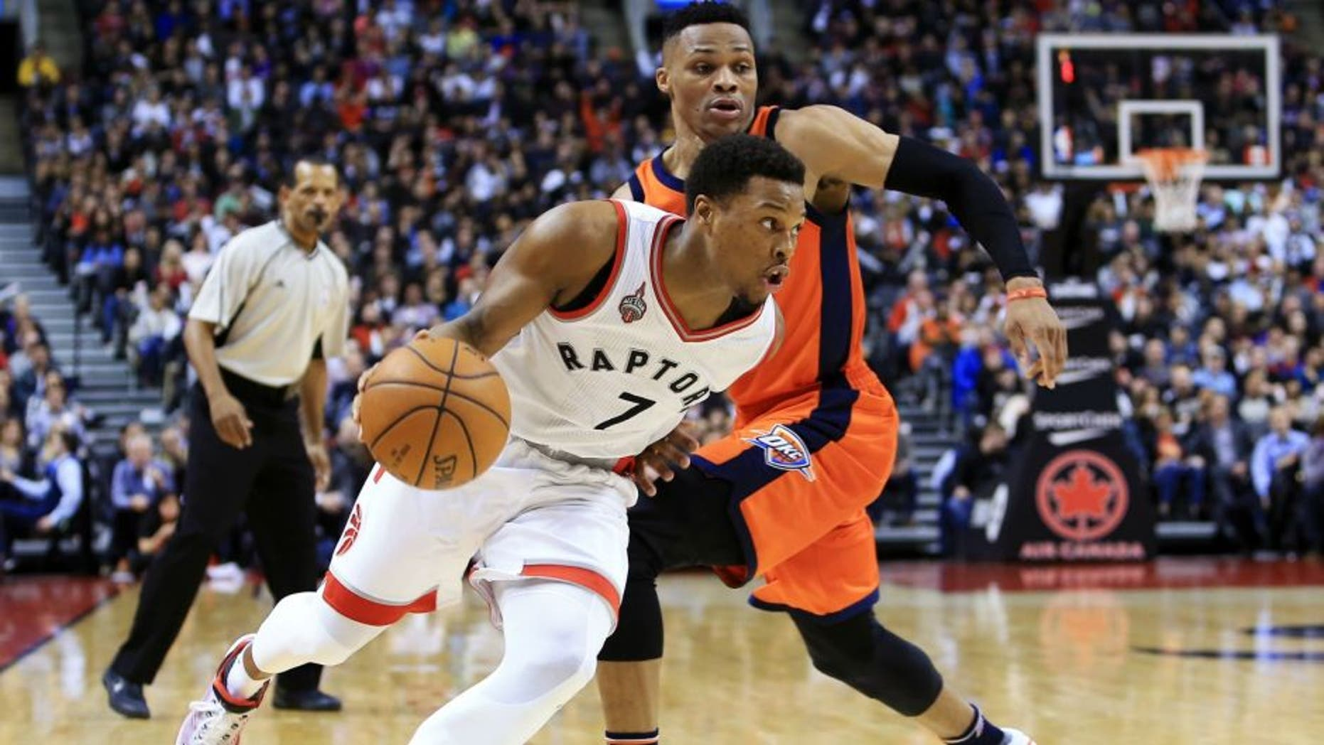 TORONTO, ON - MARCH 28: Kyle Lowry #7 of the Toronto Raptors dribbles the ball past Russell Westbrook #0 of the Oklahoma City Thunder during the second half of an NBA game at the Air Canada Centre on March 28, 2016 in Toronto, Ontario, Canada. NOTE TO USER: User expressly acknowledges and agrees that, by downloading and or using this photograph, User is consenting to the terms and conditions of the Getty Images License Agreement. (Photo by Vaughn Ridley/Getty Images)