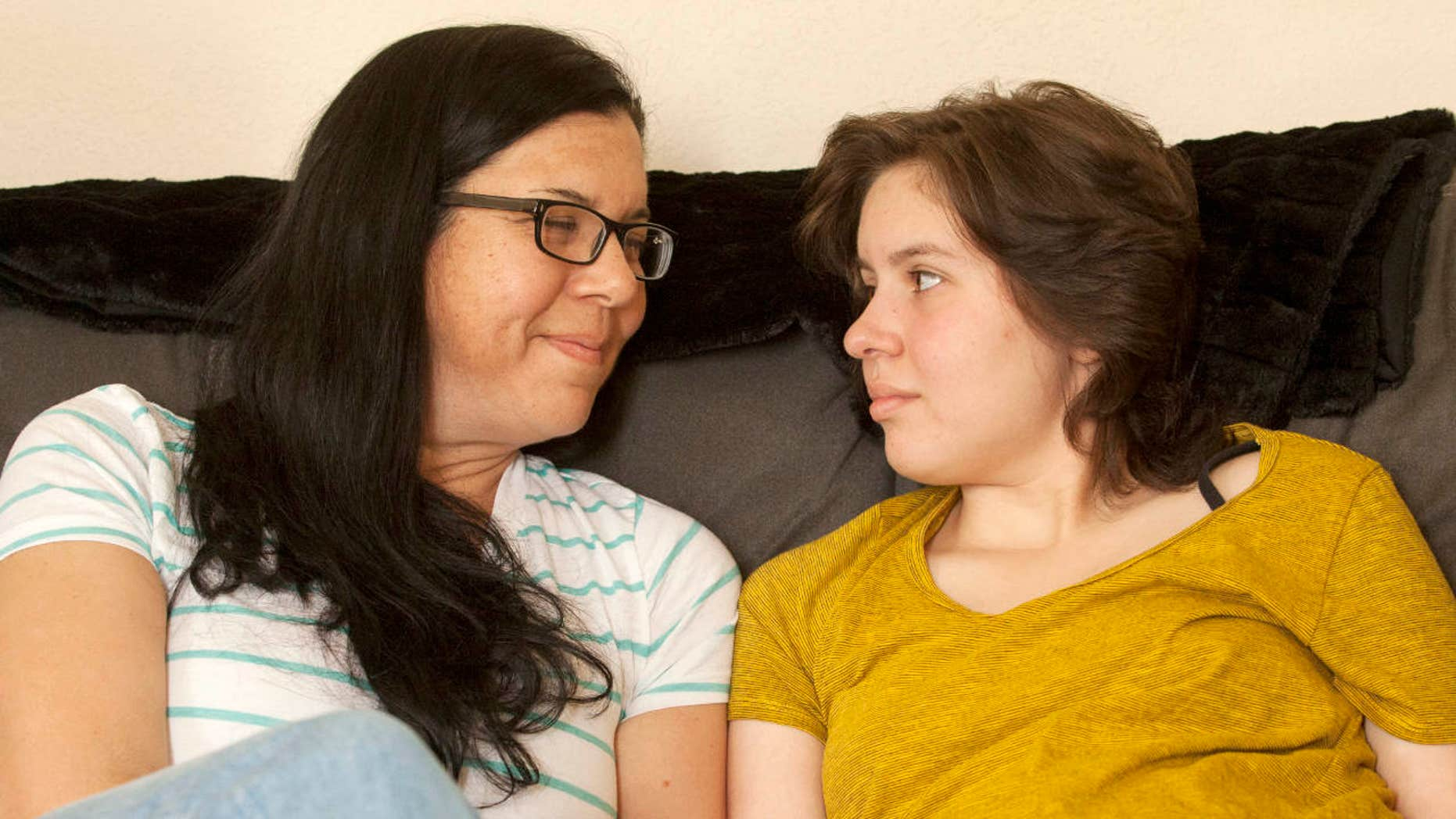 In this May 23, 2017 photo, Laura Polanco and daughter, Meredith Erck comfort each other while recalling months of fighting Erck's brain tumor while she tried to complete her high school course work in Rapid City, S.D.