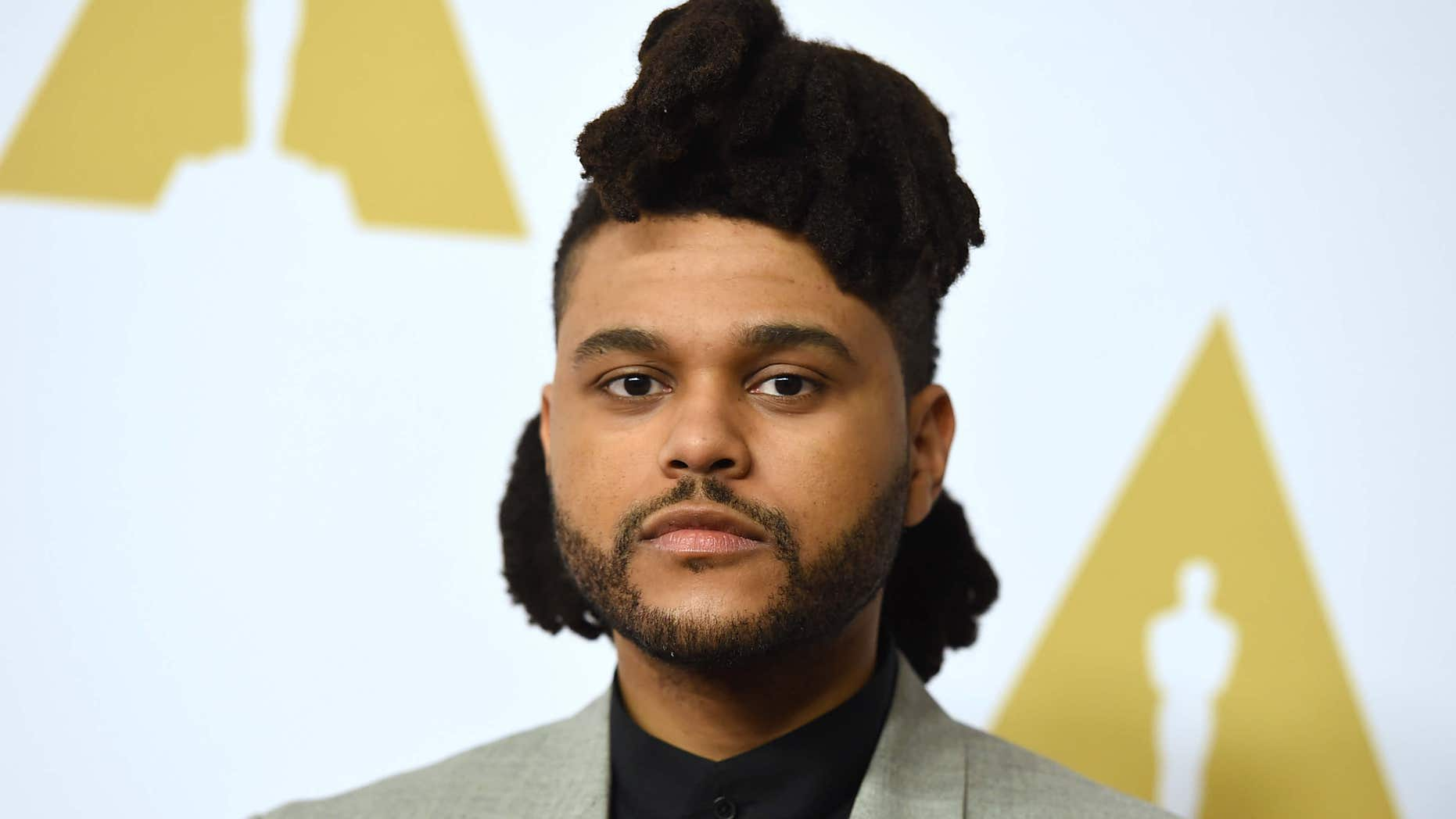 FILE - In this Feb. 8, 2016 file photo, The Weeknd arrives at the 88th Academy Awards nominees luncheon in Beverly Hills, Calif.