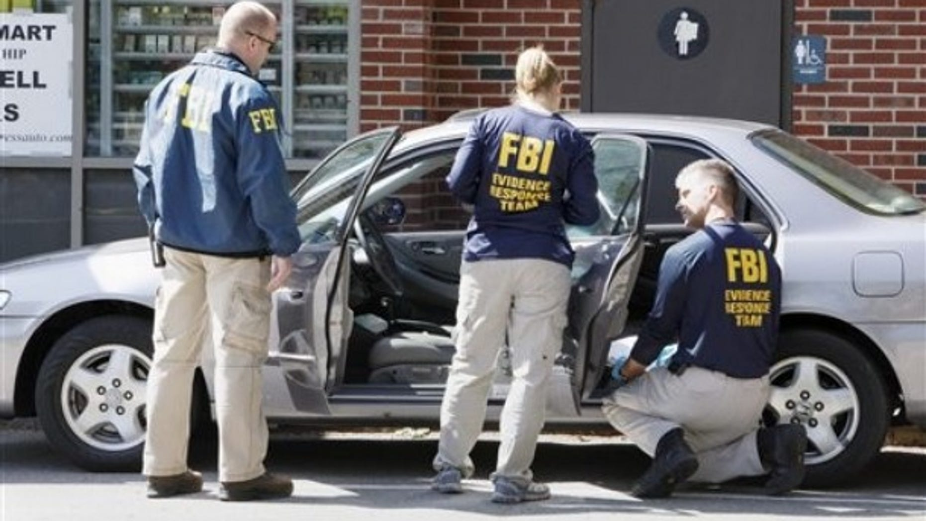May 13: FBI investigators search a car at a service station in Brookline, Mass., in connection with the failed New York Times Square car bomb (AP).