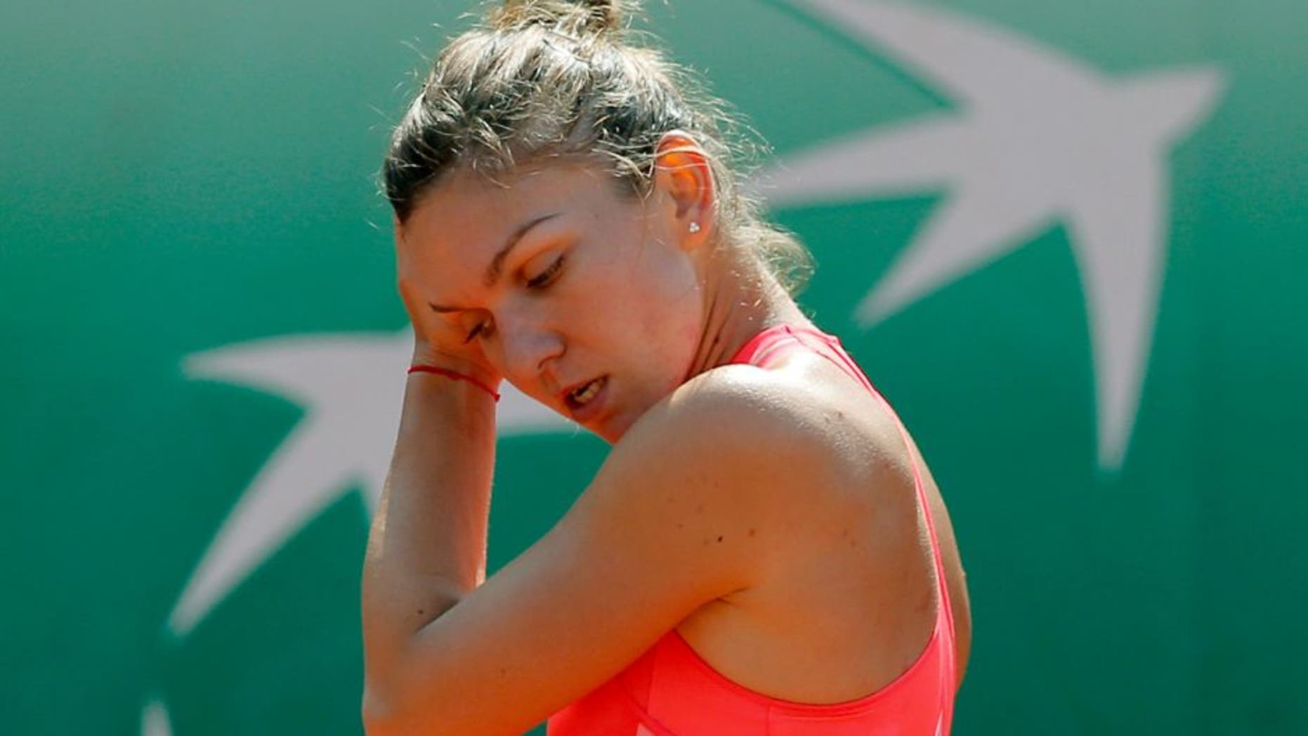 Romania's Simona Halep holds her head after missing a return in the second round match of the French Open tennis tournament against Croatia's Mirjana Lucic-Baroni at the Roland Garros stadium, in Paris, France, Wednesday, May 27, 2015. Lucic-Baroni won in two sets 7-5, 6-1. (AP Photo/Christophe Ena)