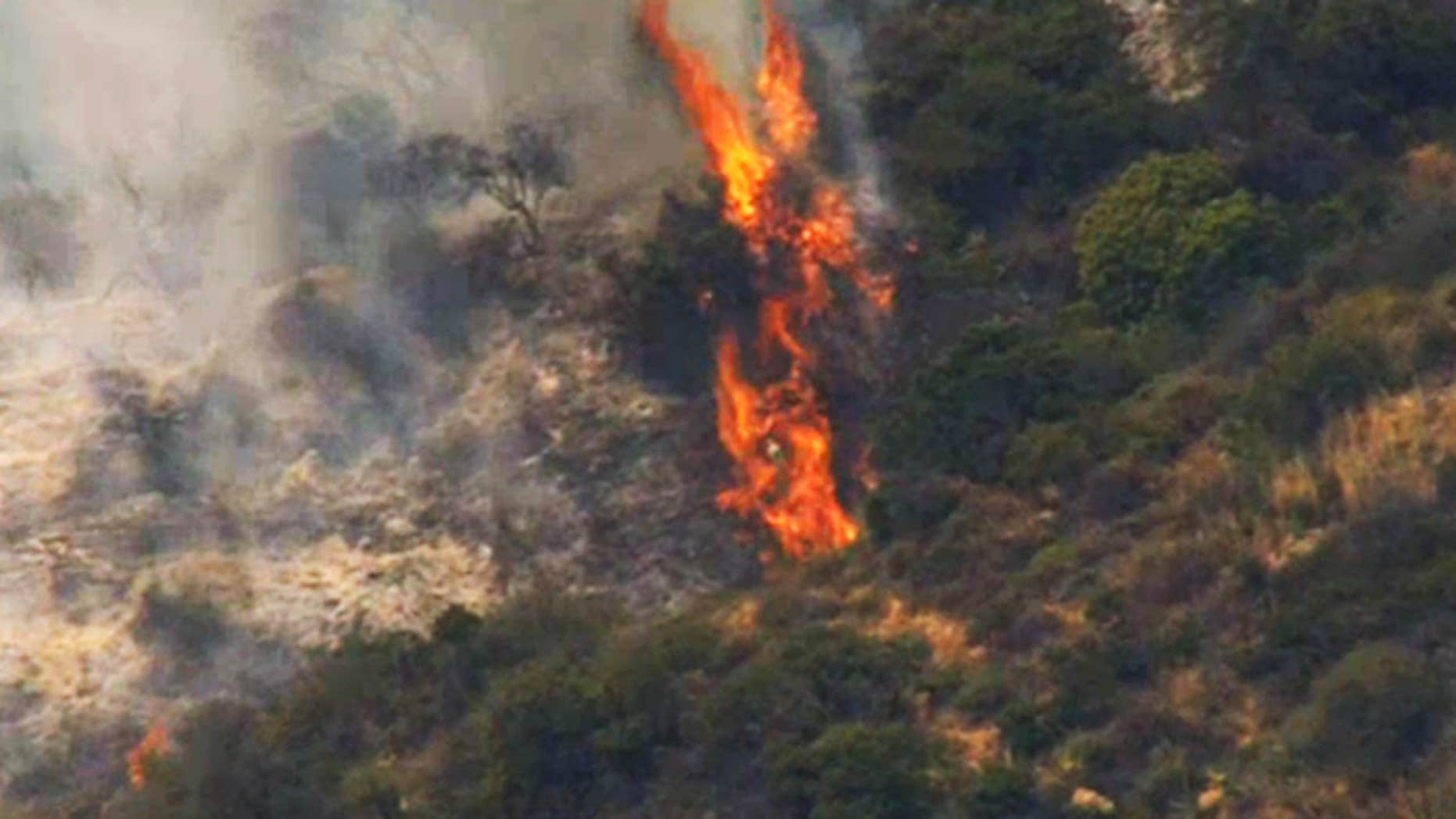 This still photo from video provided by KNBC-TV shows a hot spot from a wildfire above Mandeville Canyon Road in the Brentwood area of Los Angeles Sunday, May 28, 2017.
