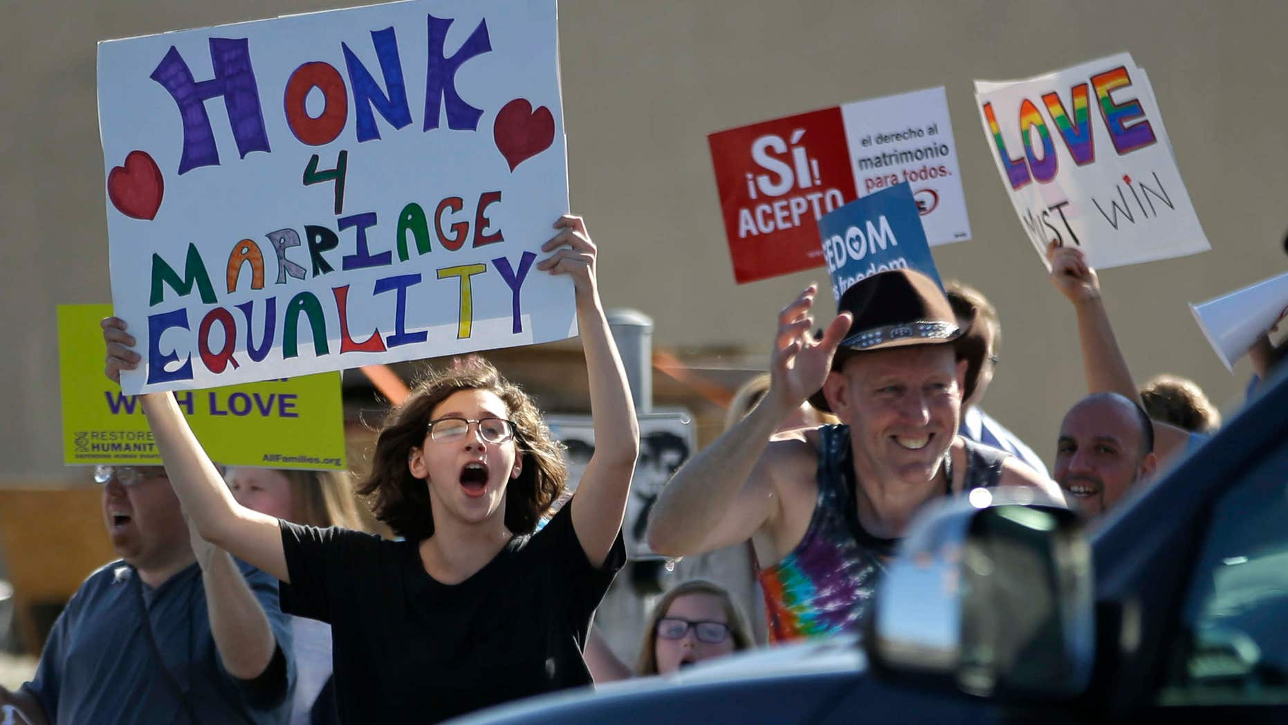 April 28, 2015: Same-sex marriage supporters hold signs encouraging drivers to honk in support of marriage equality during a rally.