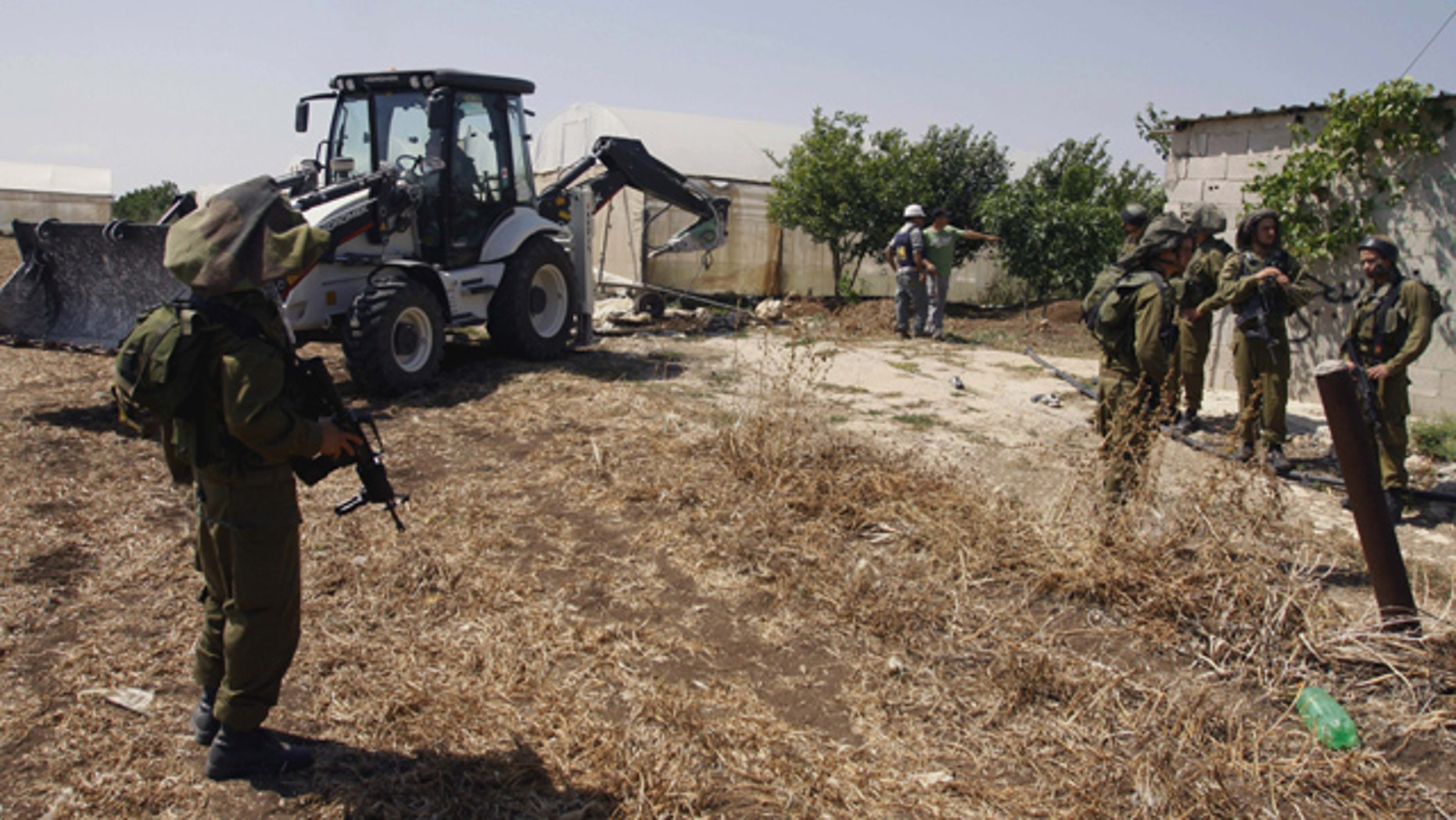 May 29: Israeli soldiers guard as a military tractor destroy wells used by Palestinian farmers for agricultural irrigation near the West Bank village of Kfar Dan west of Jenin.