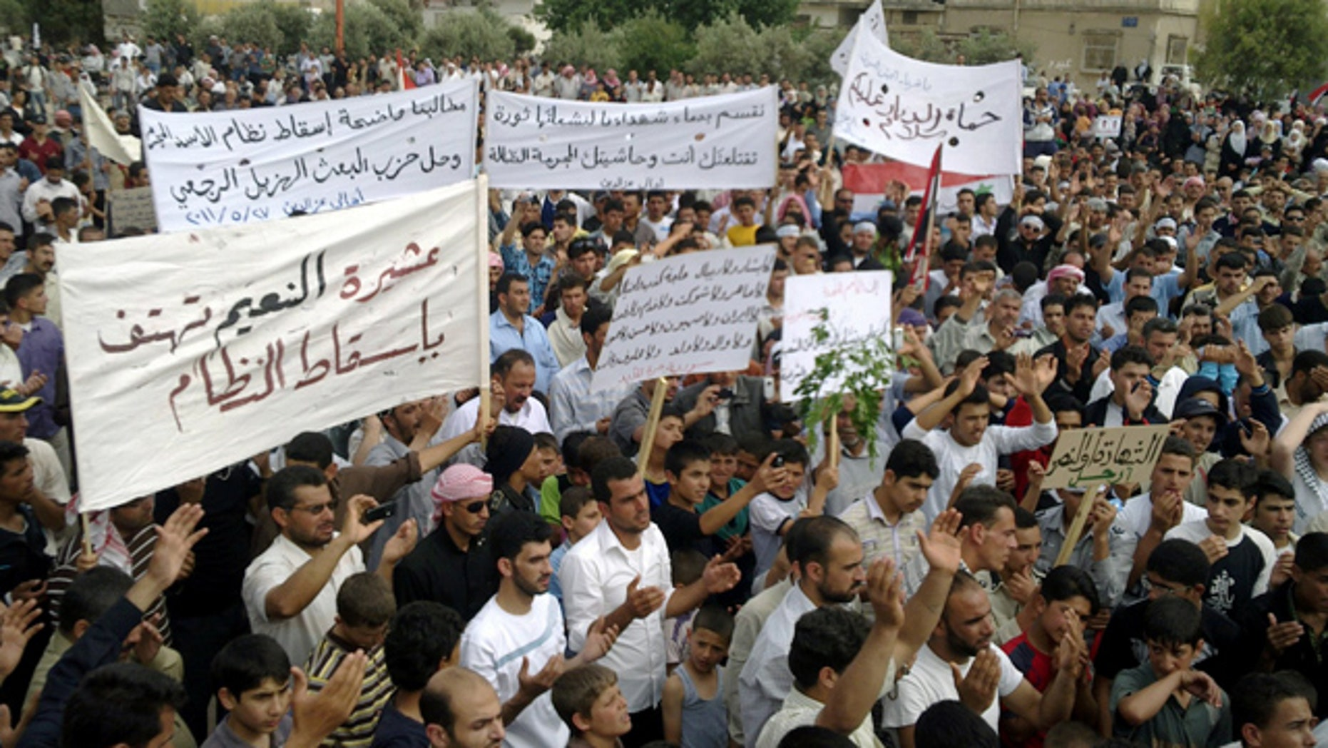 May 27: In this citizen journalism image made on a mobile phone and provided by Shaam News Network, Syrian anti-regime protesters carry banners during a rally in Talbiseh, in the central province of Homs, Syria.