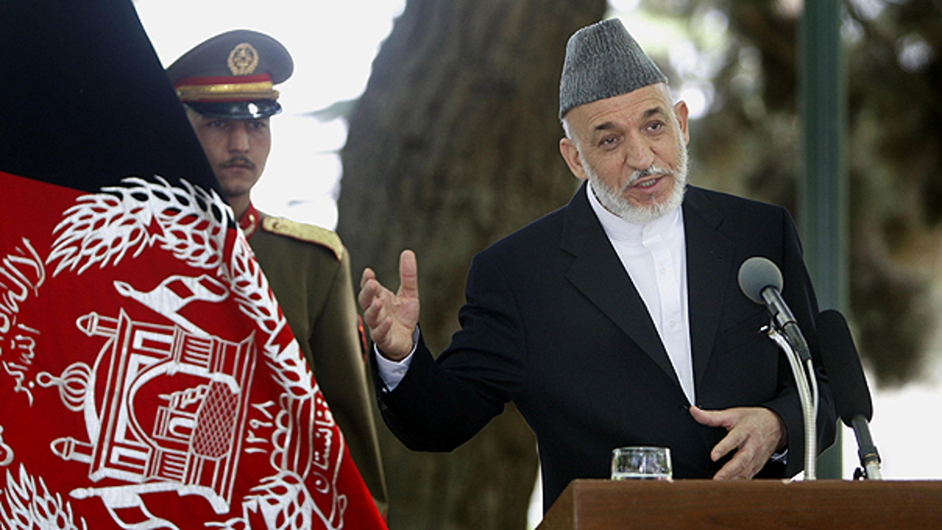 May 24: Afghan President Hamid Karzai, right, addresses a joint press conference with NATO Secretary General Anders Fogh Rasmussen, unseen, as an Afghan Presidential bodyguard holds the Afghan flag, left, at the Presidential palace in Kabul, Afghanistan.