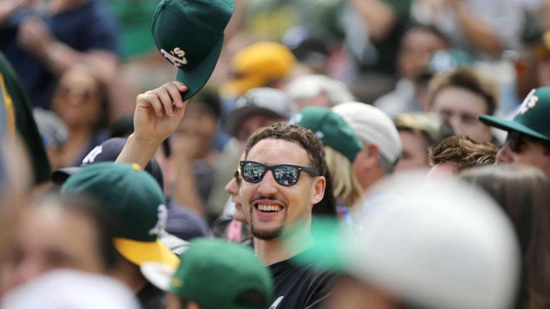 May 31, 2015; Oakland, CA, USA; Golden State Warriors guard Klay Thompson smiles and waves his Oakland Athletics hat during the third inning against the New York Yankees at O.co Coliseum. Mandatory Credit: Kelley L Cox-USA TODAY Sports