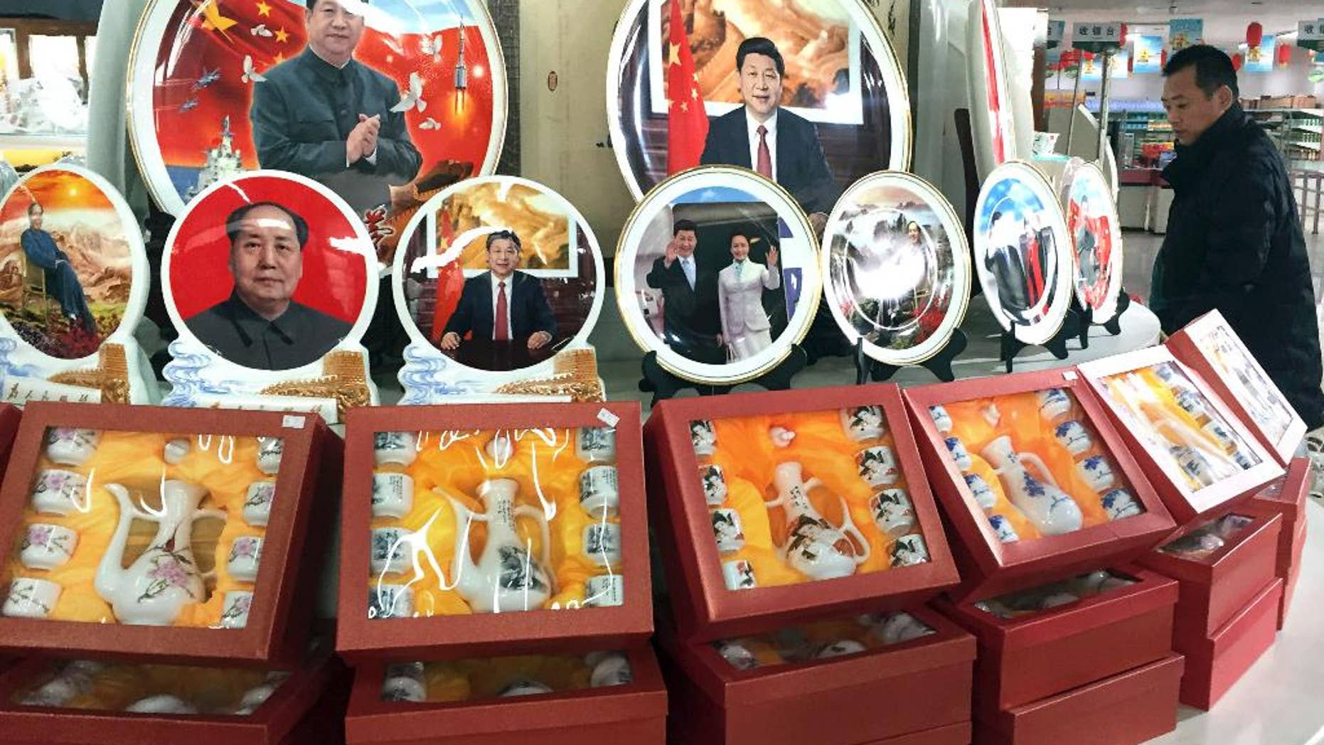In this photo taken Friday, Dec. 30, 2016, a Chinese man walks past ceramic plates with images of Chinese President Xi Jinping displayed at a rest stop near Beijing. During his annual New Year Eve's speech, Chinese President Xi Jinping says his government will continue to focus on poverty alleviation at home and resolutely defending China's territorial rights on the foreign front. (AP Photo/Ng Han Guan)