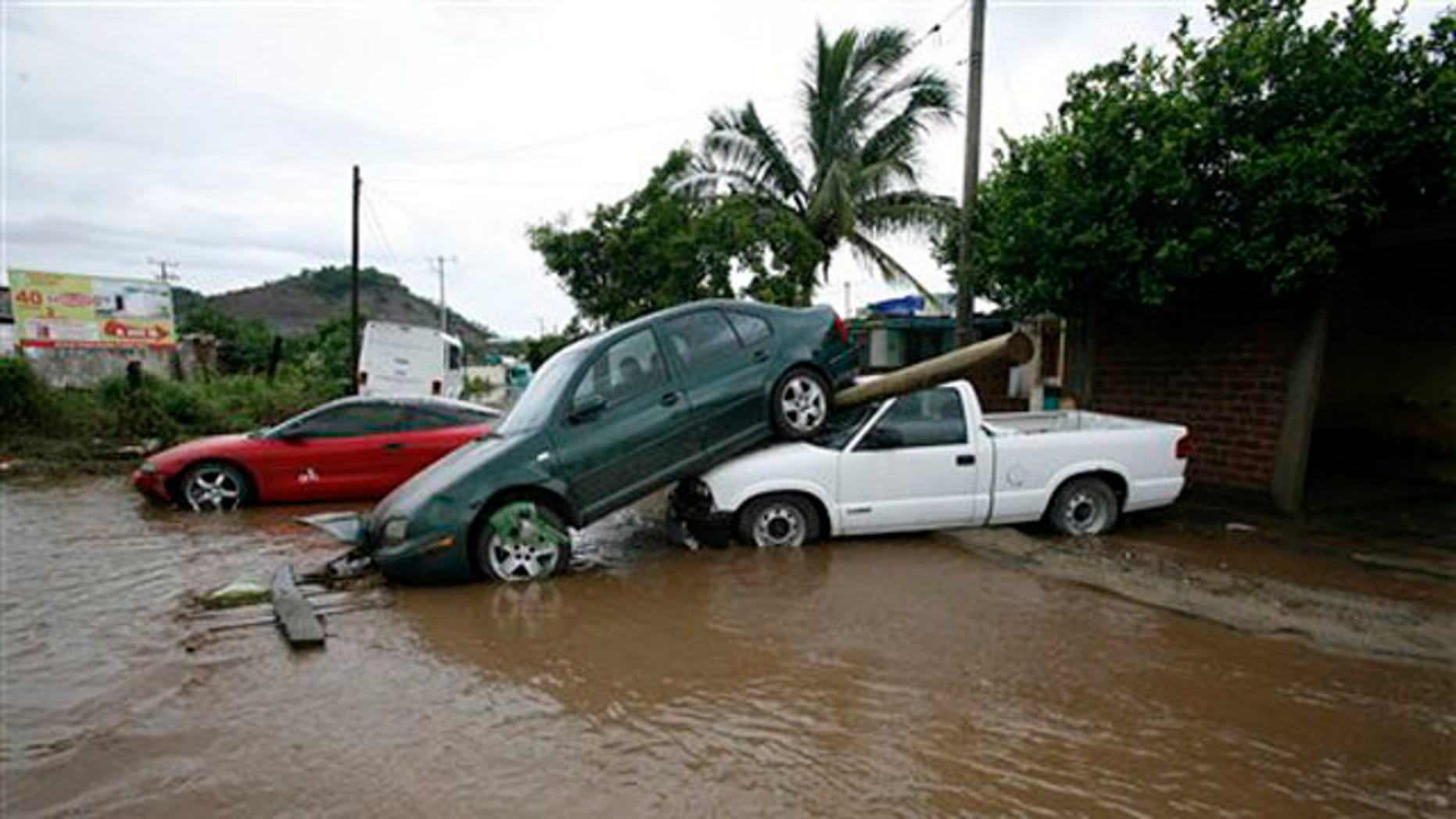 Cars pile up after being dragged by flood waters in Villa de Coral, Mexico, Wednesday Oct. 12, 2011.