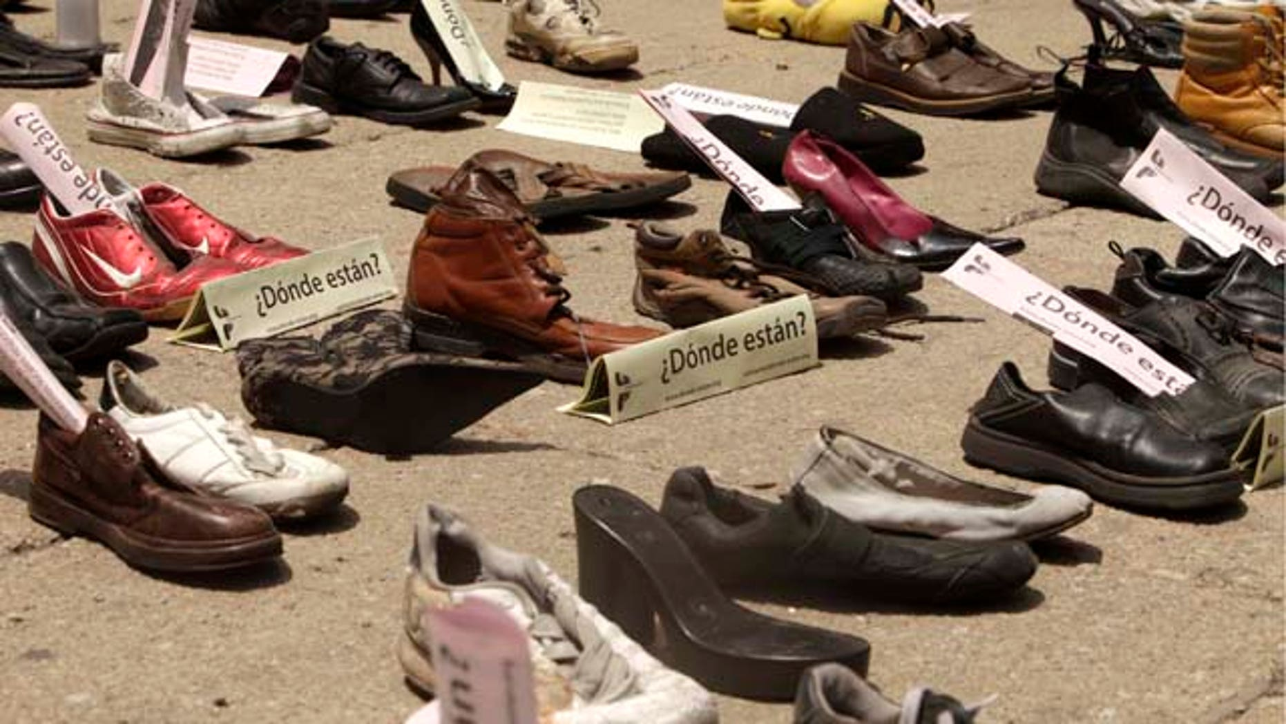 """Shoes with signs that read in Spanish: """"Where are them?"""" are displayed right outside the Senate building during a demonstration to protest against violence in Mexico City, Sunday Aug. 14, 2011. The continuing tide of drug-related killings in Mexico has drawn thousands of protesters to march against violence. (AP Photo/Arnulfo Franco)"""