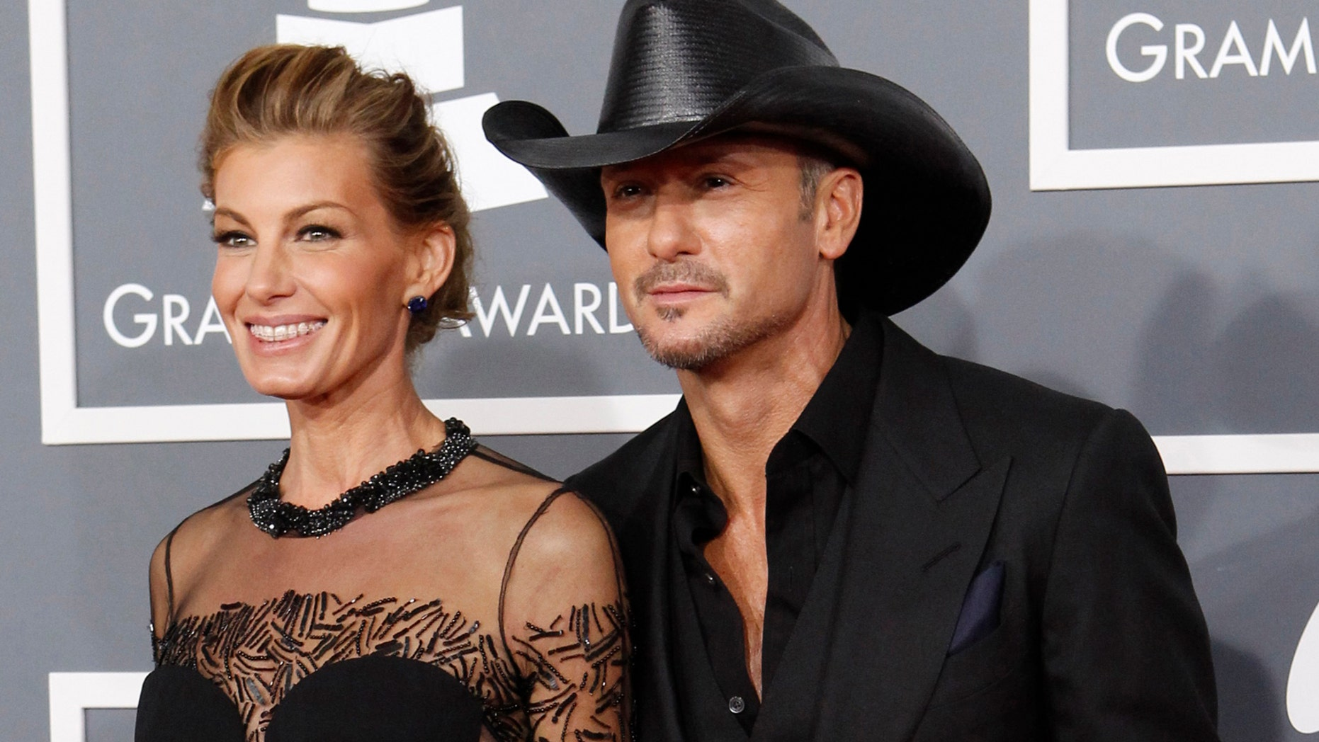 Country singers Faith HIll and her husband Tim McGraw arrive at the 55th annual Grammy Awards in Los Angeles, California February 10, 2013. REUTERS/Mario Anzuoni (UNITED STATES - Tags: ENTERTAINMENT) (GRAMMYS-ARRIVALS) - RTR3DM59