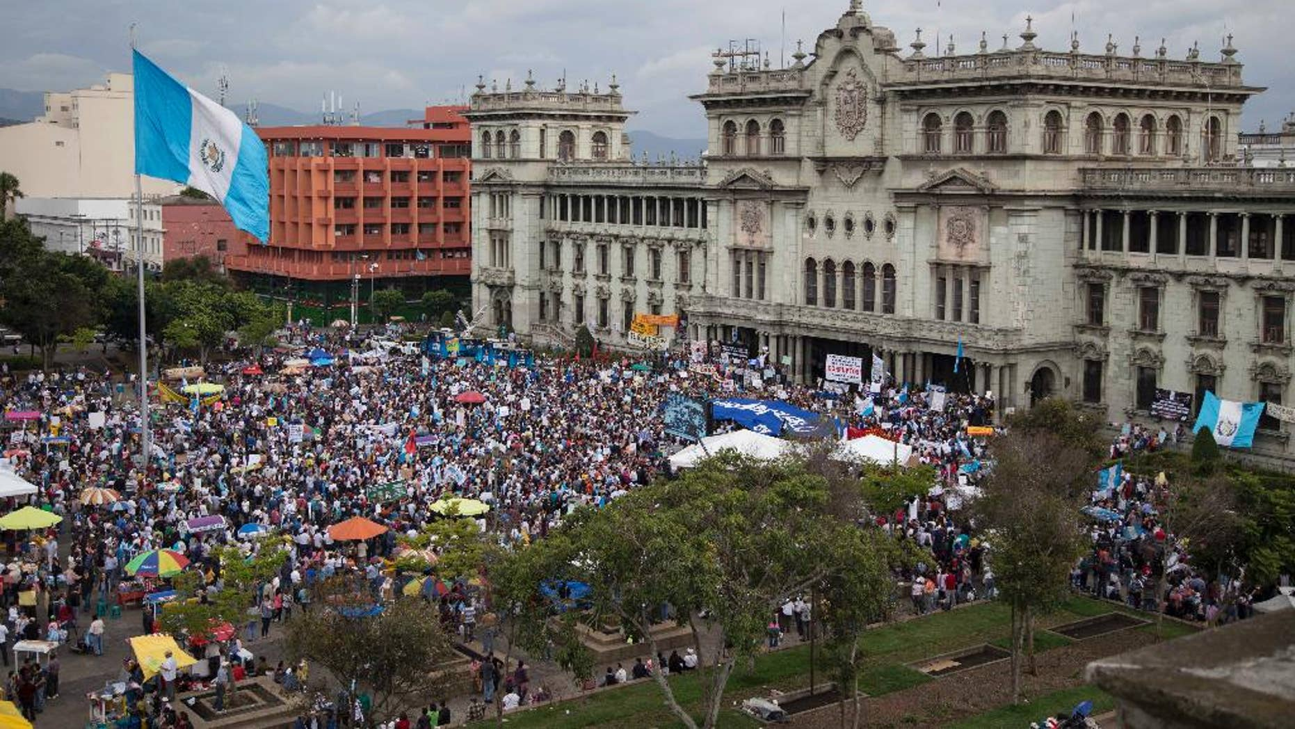 Demonstrators gather outside the National Palace demanding the resignation of Guatemala President Otto Perez Molina, in Guatemala City, Saturday, June 13, 2015. Guatemala's Supreme Court has given the go-ahead for congress to decide whether to remove Perez Molina's immunity from prosecution in a corruption scandal. (AP Photo/Luis Soto)