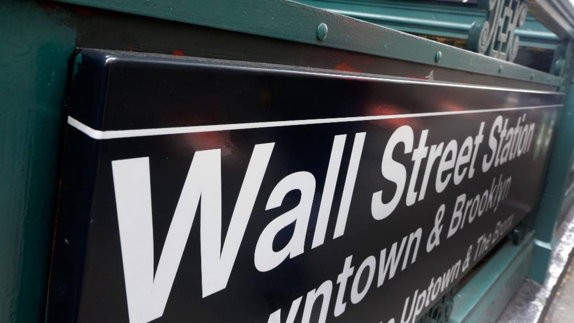 FILE-This Oct. 29, 2014 file photo shows the Wall Street subway stop on Broadway, in New York's Financial District.  U.S. stocks are falling broadly in early trading on Friday, April 17, 2015,  following steep declines in Europe and some results from big U.S. companies. Nine of the 10 industry groups of the Standard and Poor's 500 are down, led by information technology companies.  (AP Photo/Richard Drew)