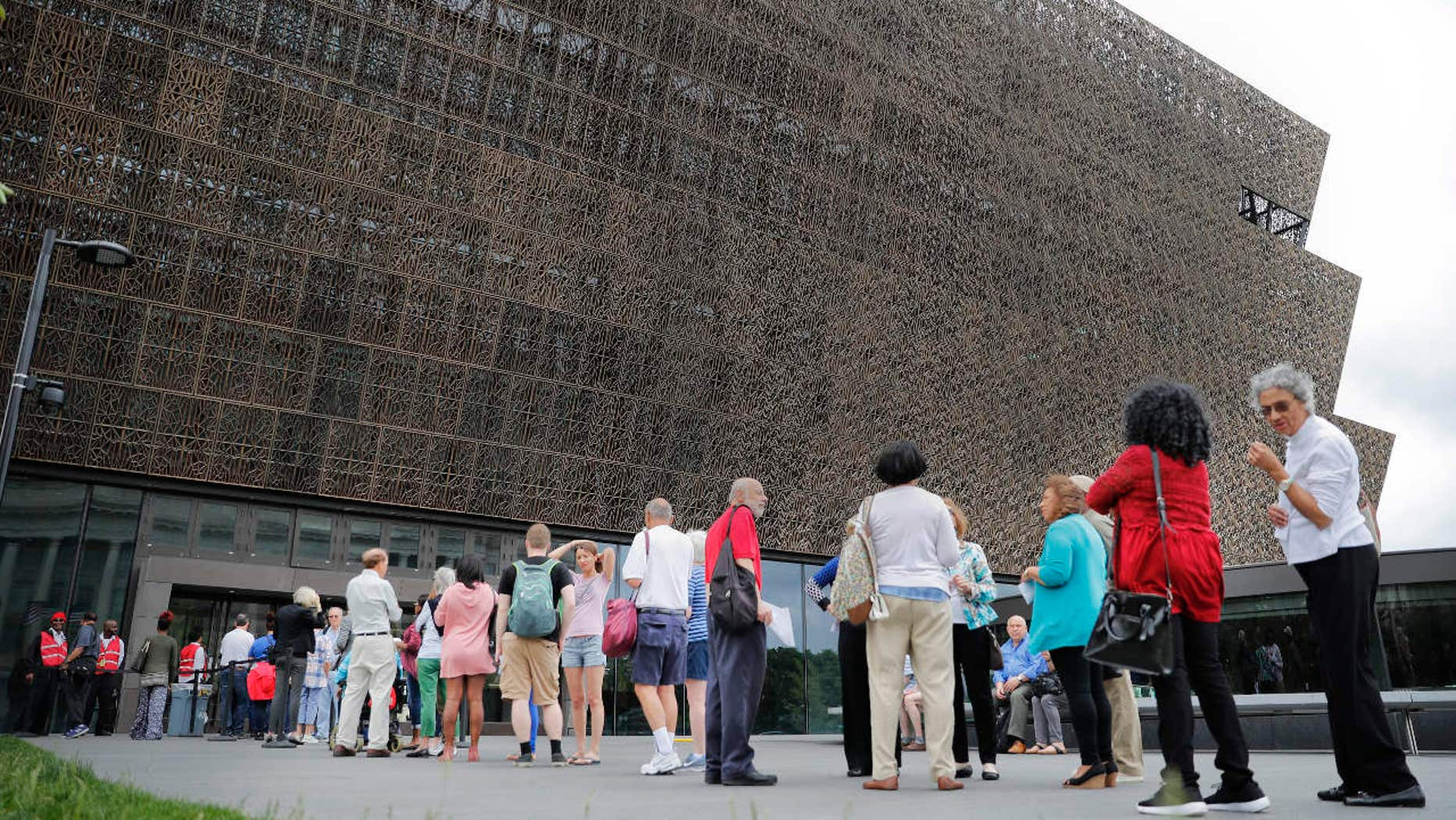 FILE- In this May 1, 2017, file photo, people wait in line to enter the Smithsonian National Museum of African American History and Cultural on the National Mall in Washington.