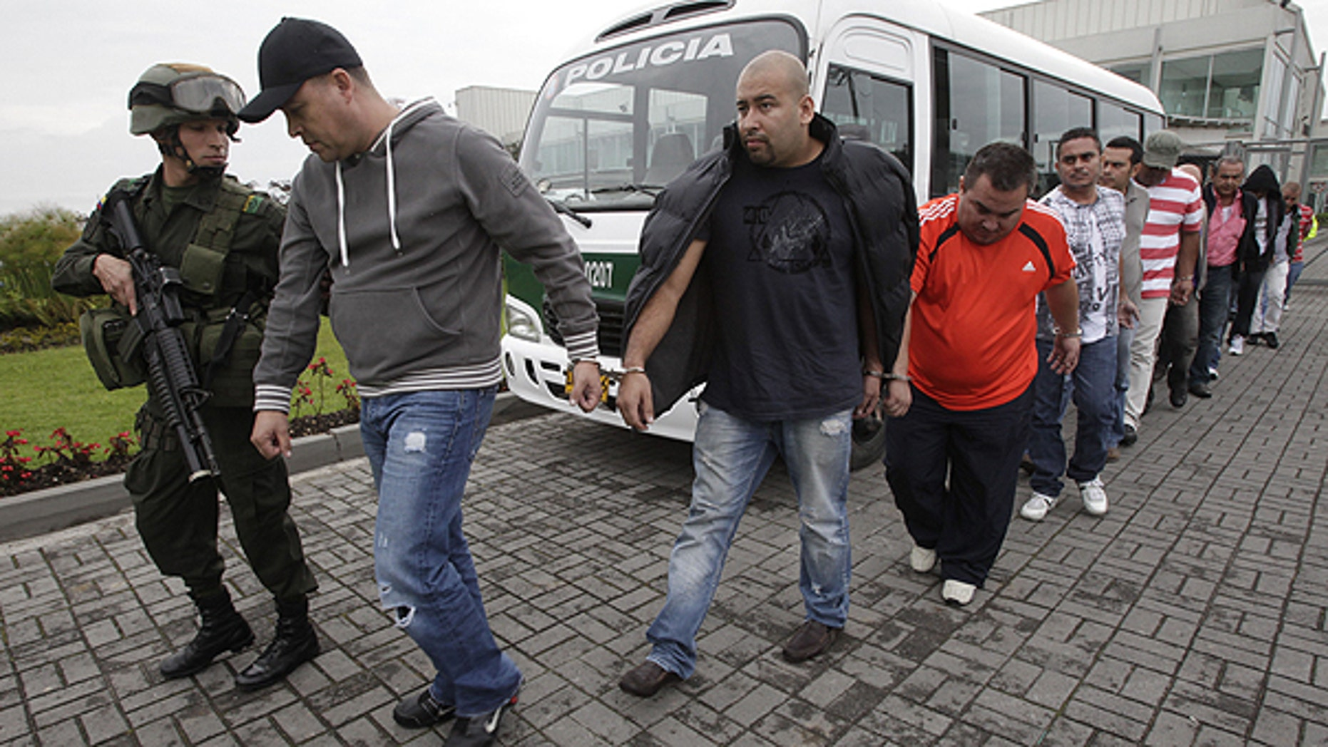 June 2: Police officers escort alleged drug traffickers at a police station in Bogota. After a five year joint investigation that began in Boston, between the Colombian and Italian police as well as the U.S. Drug Enforcement Administration, DEA, a total of twenty men, twelve in Colombia, were arrested for allegedly conspiring to smuggle cocaine and heroin, police said.