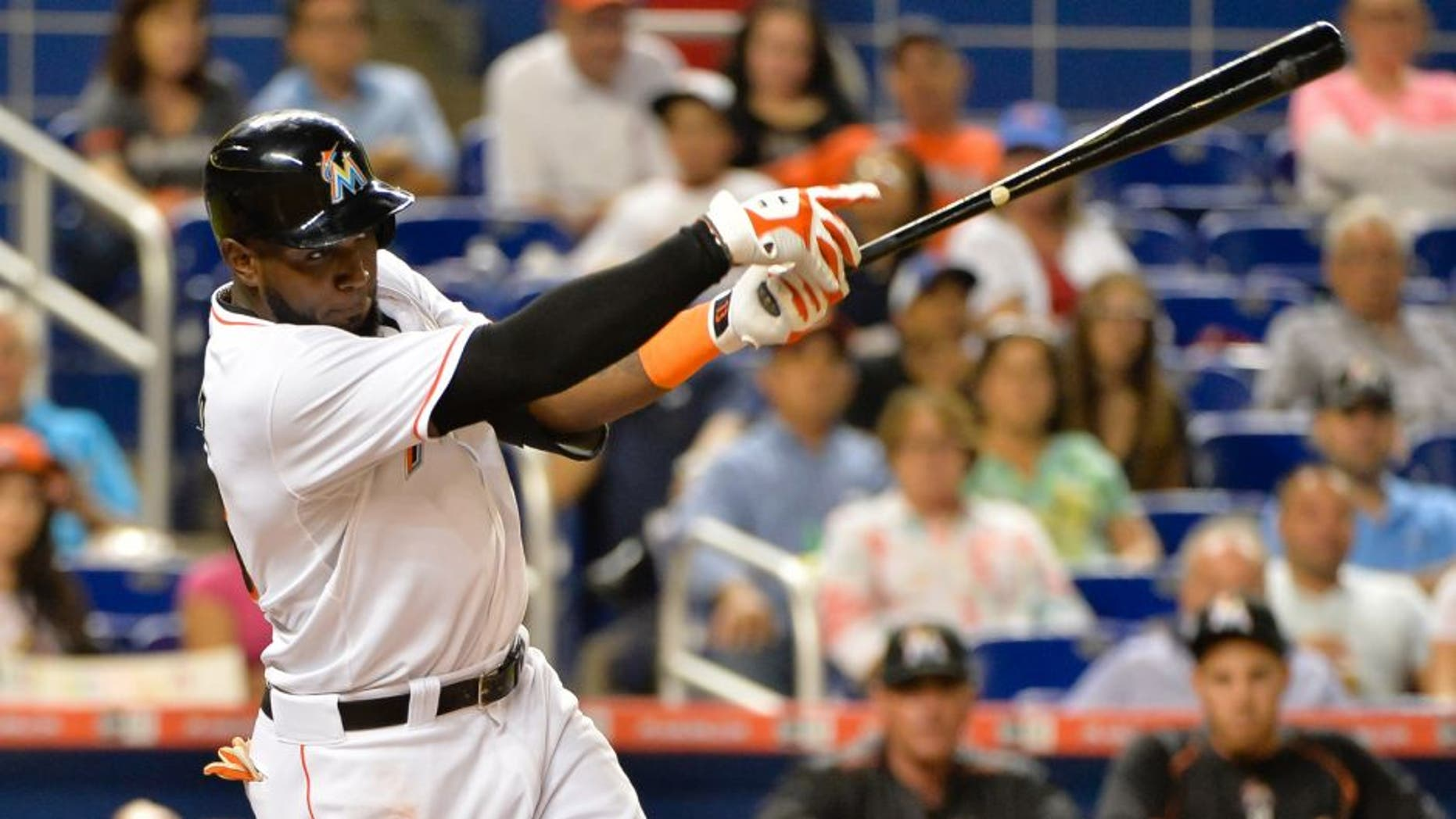 Jun 2, 2015; Miami, FL, USA; Miami Marlins center fielder Marcell Ozuna (13) connects for a base hit during the second inning against the Chicago Cubs at Marlins Park. Mandatory Credit: Steve Mitchell-USA TODAY Sports