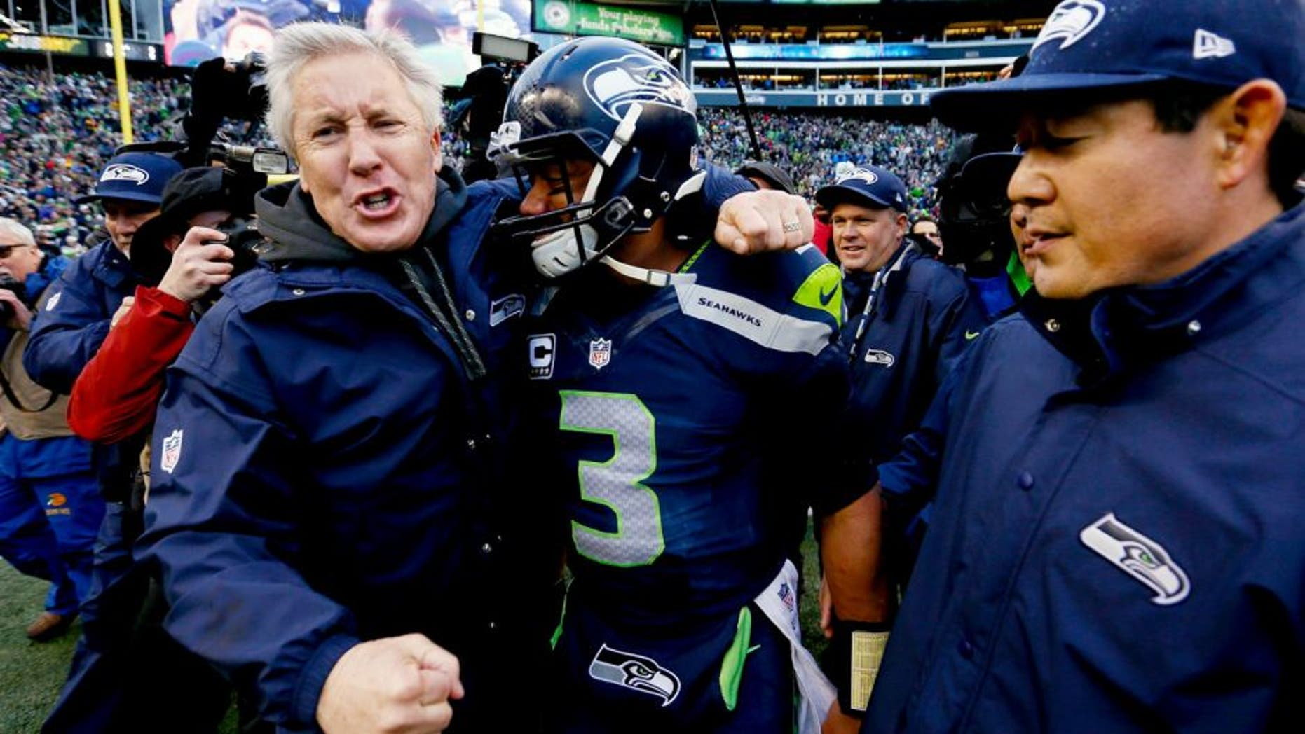 SEATTLE, WA - JANUARY 18: Head coach Pete Carroll and Russell Wilson #3 of the Seattle Seahawks celebrate after the Seahawks 28-22 victory in overtime against the Green Bay Packers during the 2015 NFC Championship game at CenturyLink Field on January 18, 2015 in Seattle, Washington. (Photo by Kevin C. Cox/Getty Images)