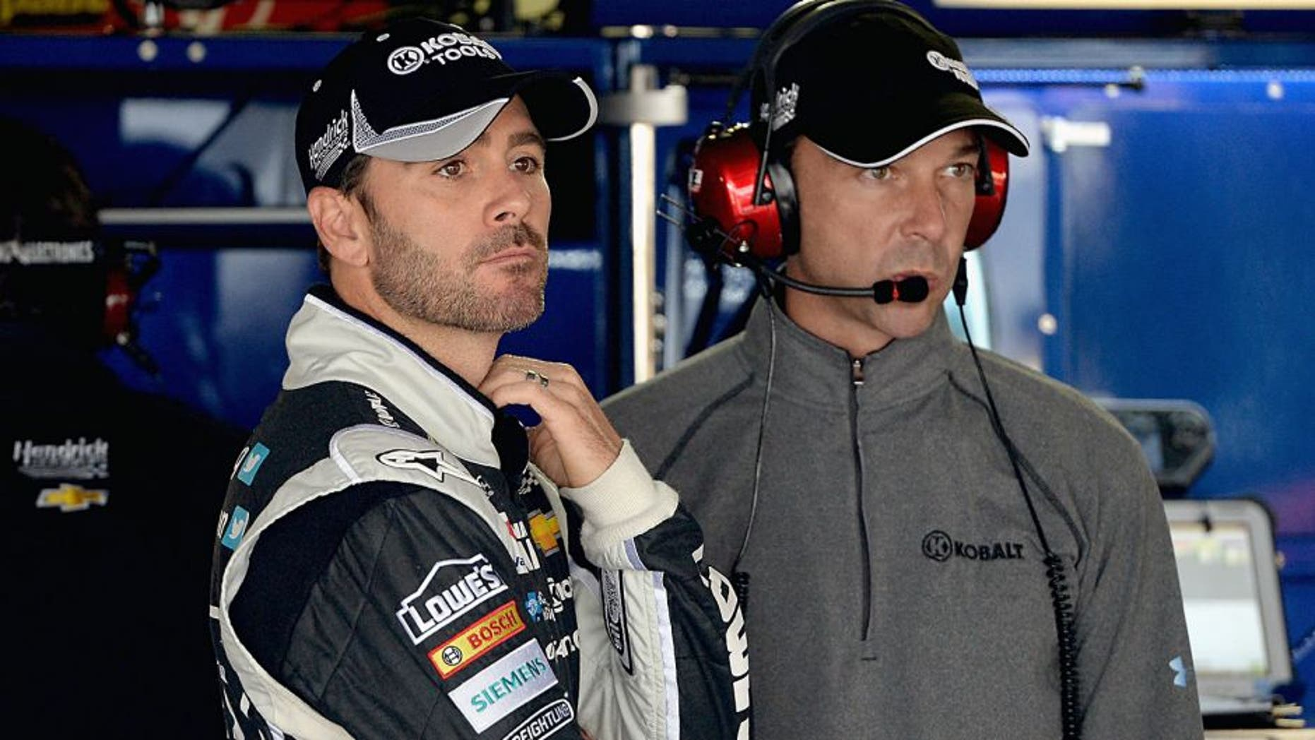 DOVER, DE - MAY 30: Jimmie Johnson, left, driver of the #48 Lowe's/Kobalt Tools Chevrolet, and crew chief Chad Knaus looks on in the garage area during practice for the NASCAR Sprint Cup Series FedEx 400 Benefiting Autism Speaks at Dover International Speedway on May 30, 2014 in Dover, Delaware. (Photo by Patrick Smith/Getty Images)