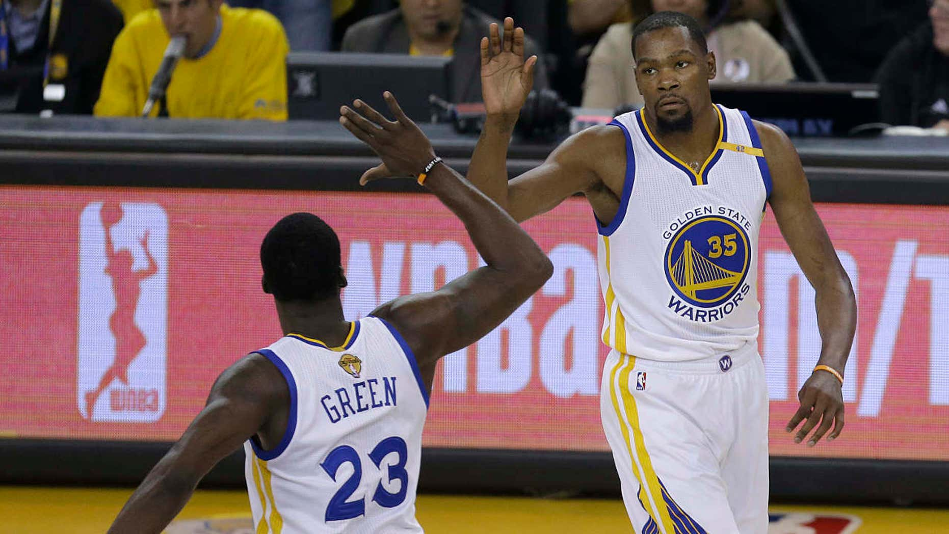 Golden State Warriors forward Kevin Durant (35) and forward Draymond Green (23) celebrate during the first half of Game 2 of basketball's NBA Finals against the Cleveland Cavaliers in Oakland, Calif., Sunday, June 4, 2017.