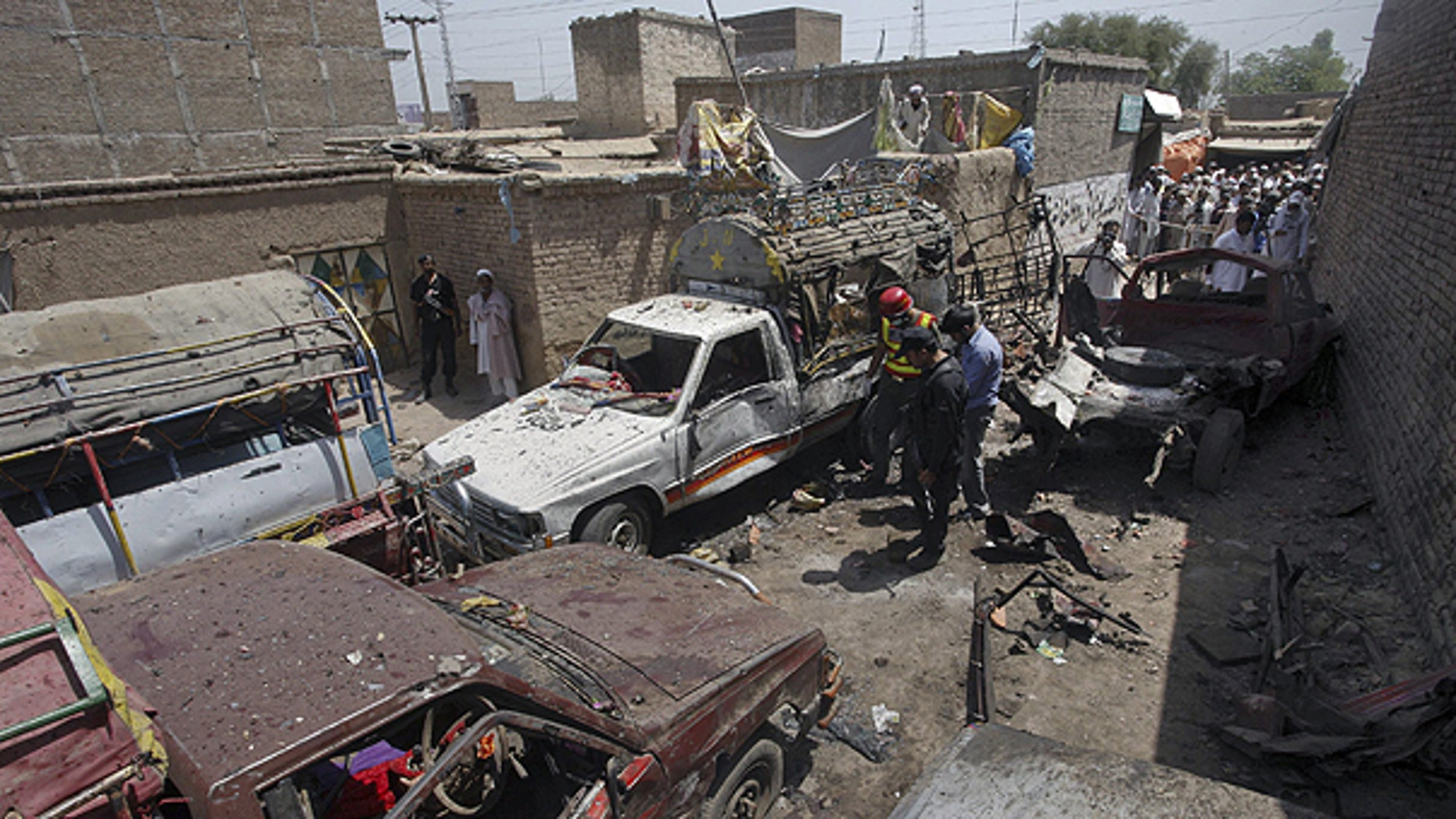 June 5: Pakistani police officer and rescue worker examine the site of a bomb blast in a bus stand in Matani near Peshawar.
