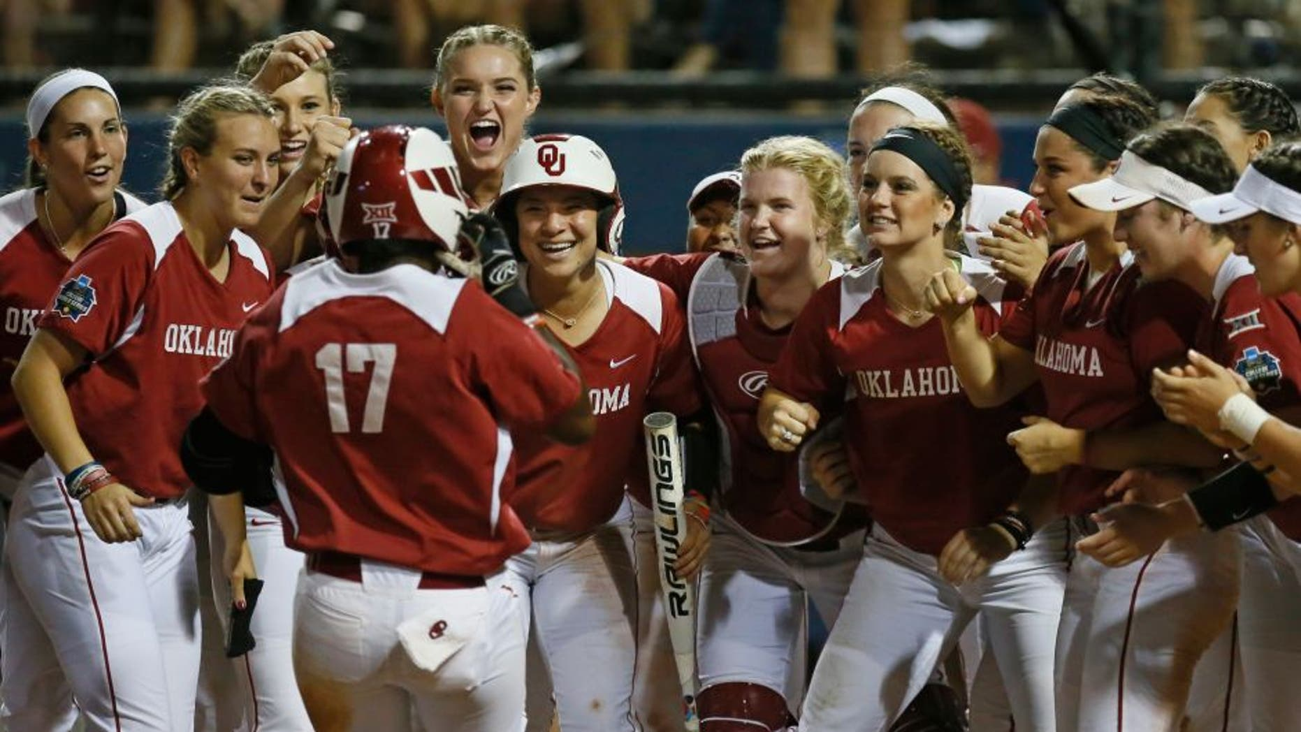 Oklahoma infielder Shay Knighten (17) is greeted at the plate by her teammates after hitting a home run in the seventh inning of an NCAA Women's College World Series softball game against LSU in Oklahoma City, Sunday, June 5, 2016. Oklahoma won 7-3. (AP Photo/Sue Ogrocki)