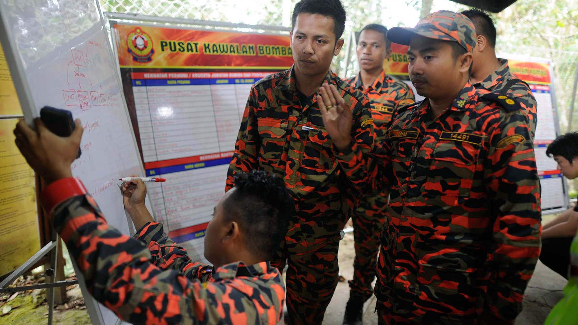 June 6, 2015: Members of the Malaysian rescue team plan as they wait for victims to be evacuated a day after an earthquake in Kundasang, a town in the district of Ranau, Malaysia.