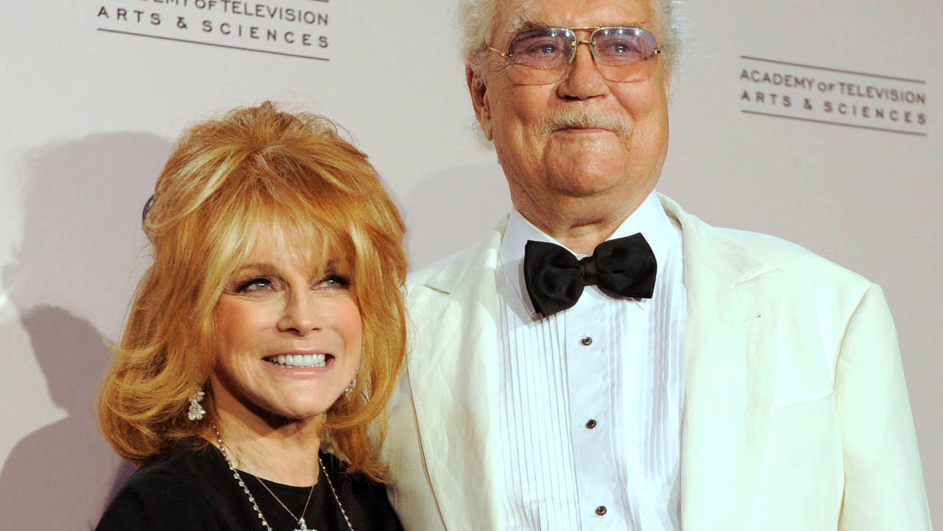 """FILE - In this Aug. 21, 2010 file photo, actress Ann-Margret winner of the award for outstanding guest actress in a drama series for """"Law & Order: Special Victims Unit"""" left, poses with her husband Roger Smith in the press room at the Creative Arts Emmy Awards in Los Angeles."""
