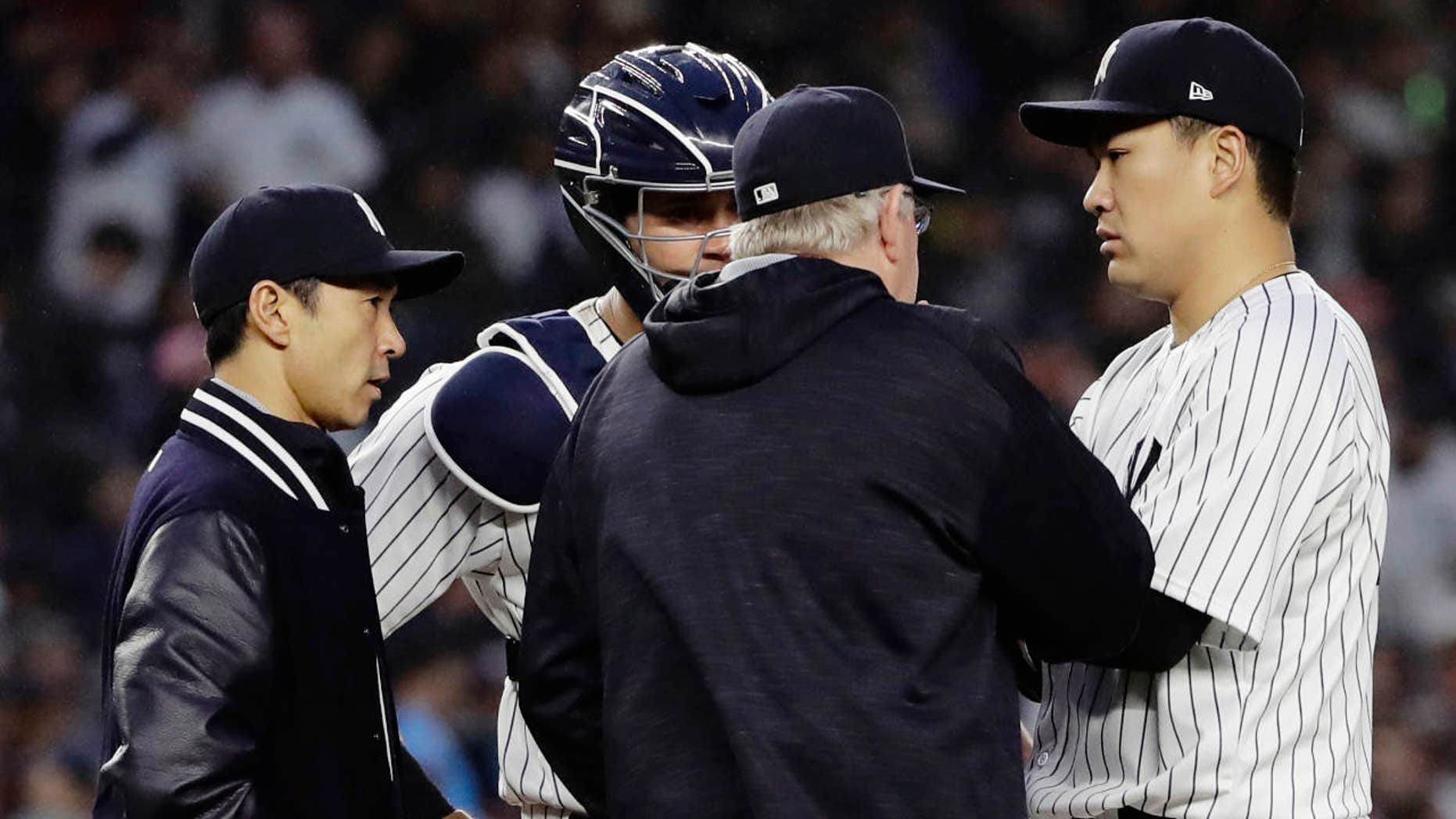 June 6, 2017: New York Yankees starting pitcher Masahiro Tanaka, of Japan, right, talks to catcher Gary Sanchez, second from left, pitching coach Larry Rothschild and translator Shingo Horie, left, during the fourth inning of a baseball game in New York.