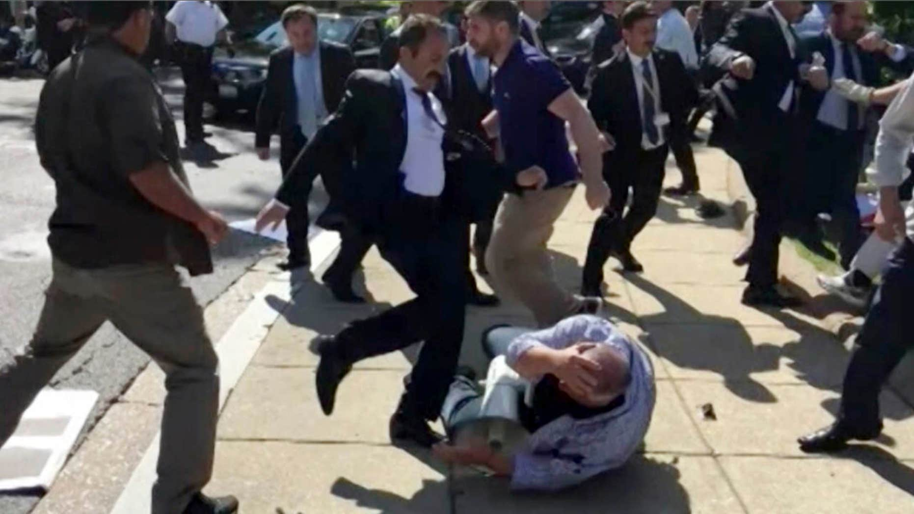 In this frame grab from video provided by Voice of America, members of Turkish President Recep Tayyip Erdogan's security detail are shown violently reacting to peaceful protesters during Erdogan's trip last month to Washington.