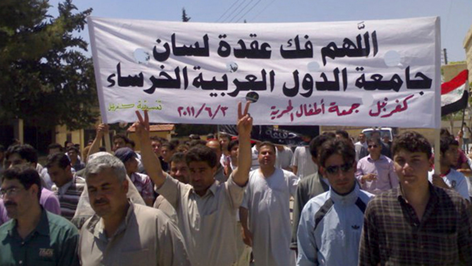 June 3: In this citizen journalism image made on a mobile phone and provided by Shaam News Network, Syrian protesters hold an Arabic banner as they march during a protest at the village of Kfar-Nebel, in the northen province of Edleb, Syria.
