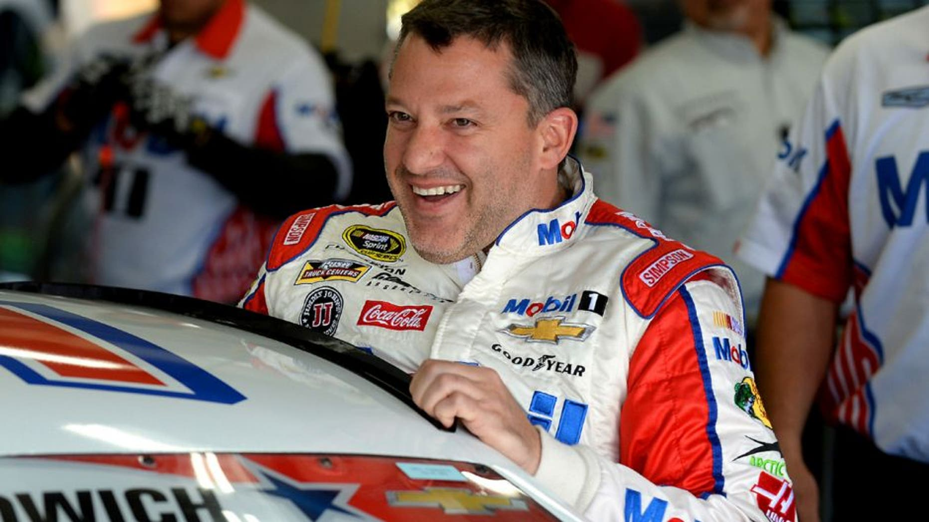 NASCAR Sprint Cup Series driver Tony Stewart laughs with members of his team as he climbs into his car for practice at Charlotte Motor Speedway in Concord, N.C., on Thursday, May 26, 2016. (Jeff Siner/Charlotte Observer/TNS via Getty Images)