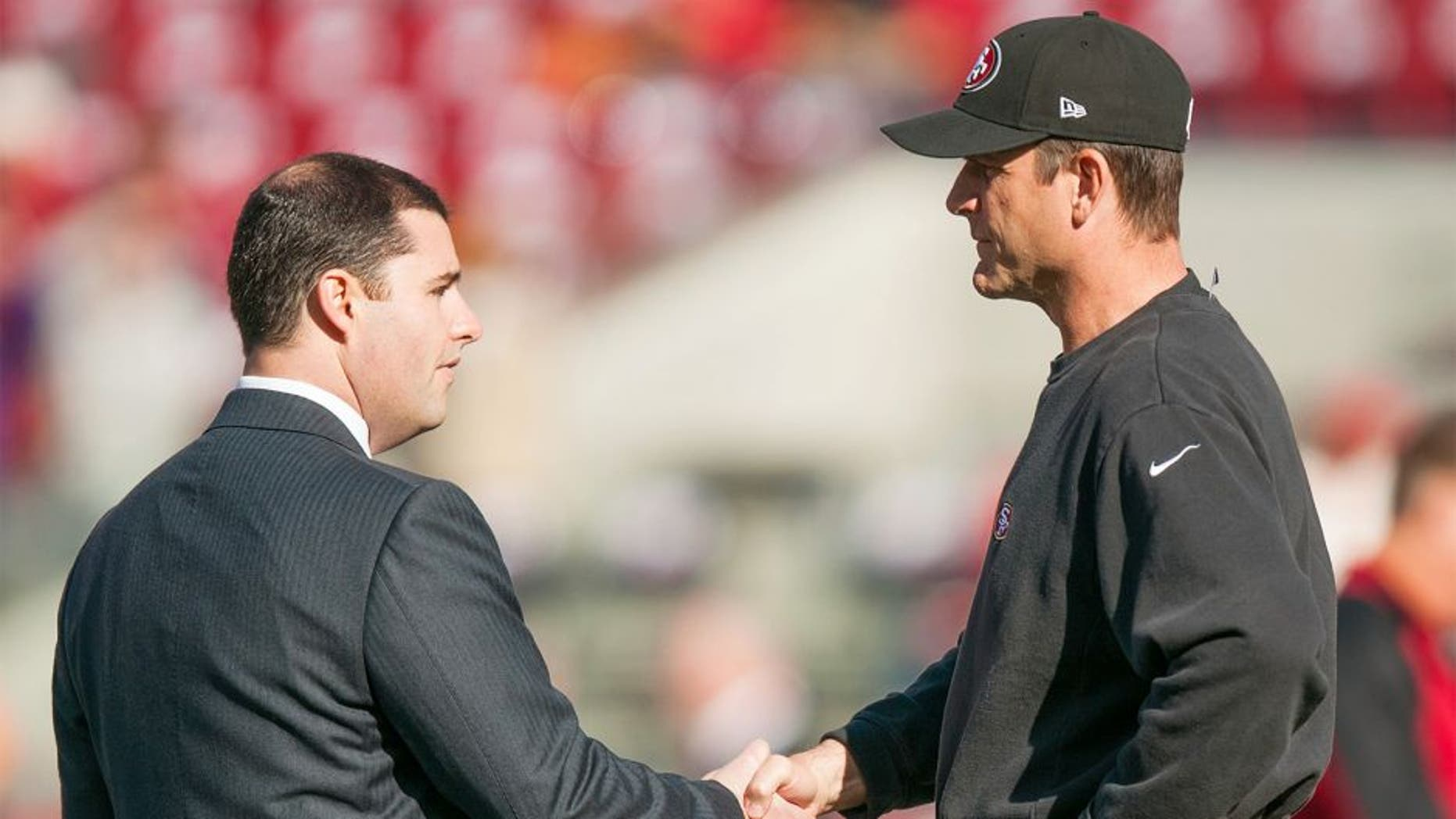 Dec 28, 2014; Santa Clara, CA, USA; San Francisco 49ers chief executive officer Jed York (left) shakes hands with head coach Jim Harbaugh (right) before the game against the Arizona Cardinals at Levi's Stadium. Mandatory Credit: Ed Szczepanski-USA TODAY Sports
