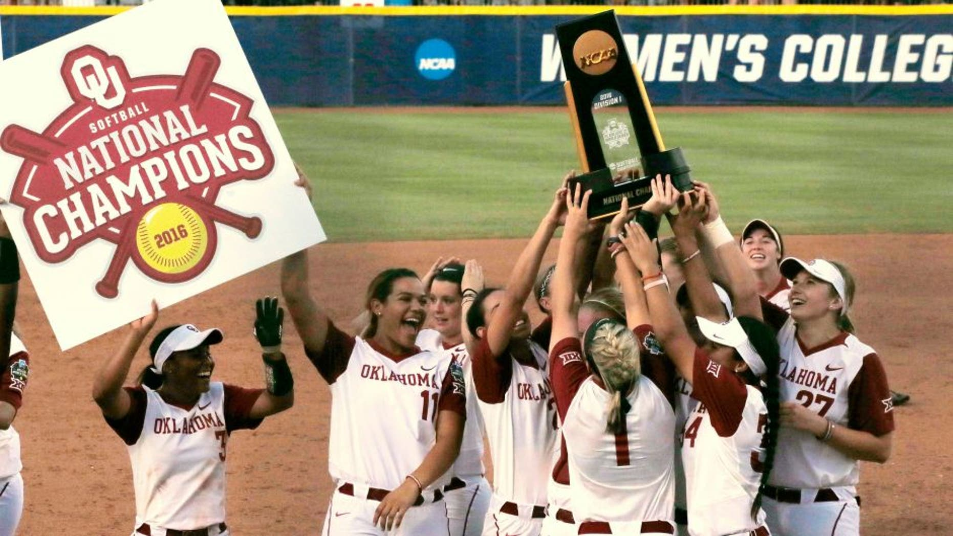 Oklahoma players celebrate with the trophy after defeating Auburn 2-1 in the deciding game of the championship series of the NCAA softball College World Series, Wednesday, June 8, 2016, in Oklahoma City. (AP Photo/Sue Ogrocki)