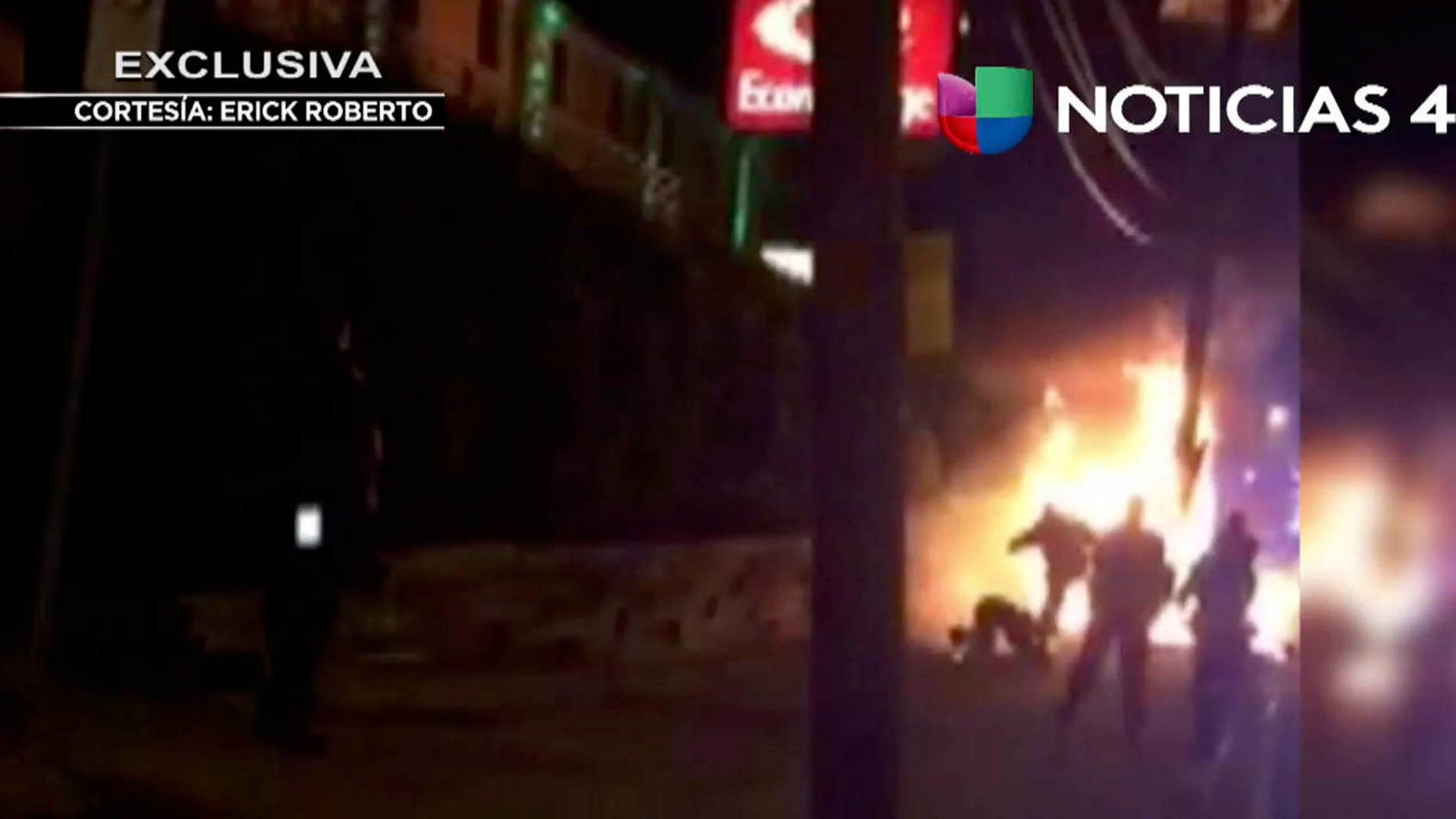 This image from video shot on June 4, 2017 shows a bystander being kicked by police officers, as he lies on the ground near flames, following an automobile chase that ended in a fiery crash, in Jersey City, N.J.
