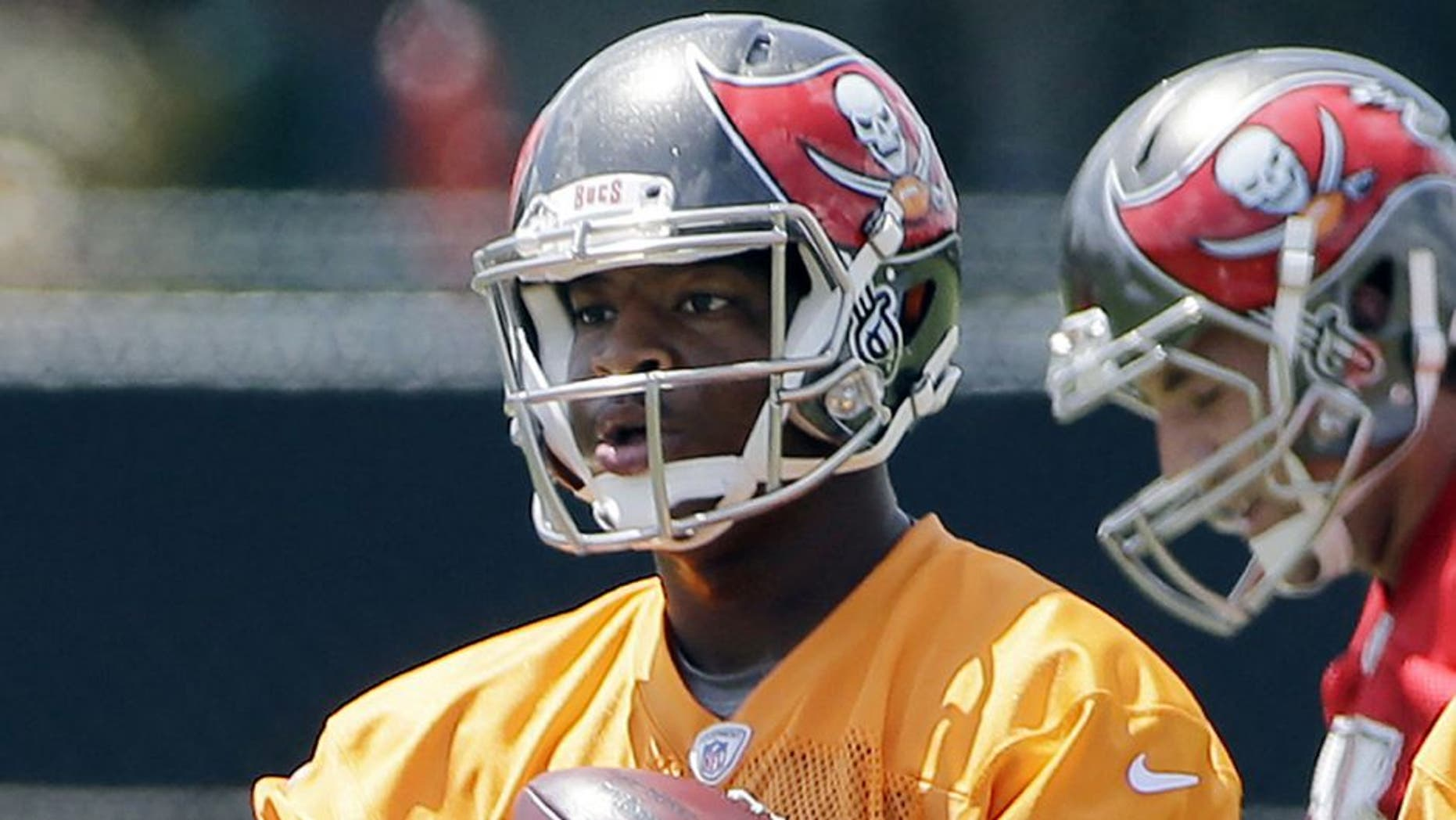 Tampa Bay Buccaneers quarterback Jameis Winston carries a handful of footballs during an NFL football organized team activity, Thursday, June 4, 2015, in Tampa, Fla. (AP Photo/Chris O'Meara)