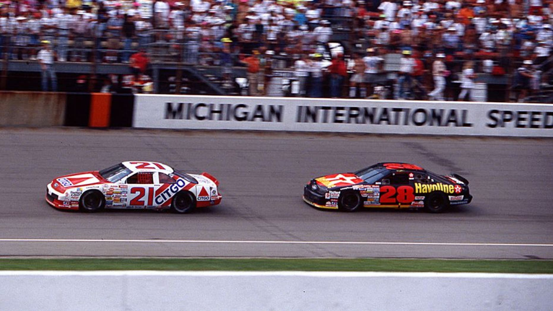 BROOKLYN, MI — August 18, 1991: Dale Jarrett (No. 21) in the Wood Brothers Citgo Ford leads Davey Allison (No. 28) to the checkered flag to win his first NASCAR Cup race, the Champion Spark Plug 400 at Michigan International Speedway. (Photo by ISC Images & Archives via Getty Images)