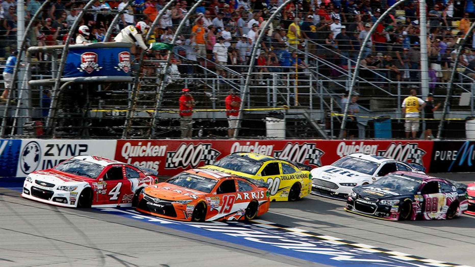 BROOKLYN, MI - JUNE 14: Carl Edwards, driver of the #19 ARRIS Toyota, and Kevin Harvick, driver of the #4 Budweiser/Jimmy John's Chevrolet, lead the field to a restart during the NASCAR Sprint Cup Series Quicken Loans 400 at Michigan International Speedway on June 14, 2015 in Brooklyn, Michigan. (Photo by Jerry Markland/Getty Images)