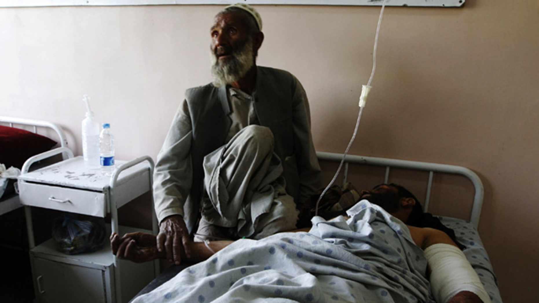 June 10: A father comforts his injured son at a hospital following a blast at wedding party in Kandahar city, Afghanistan.