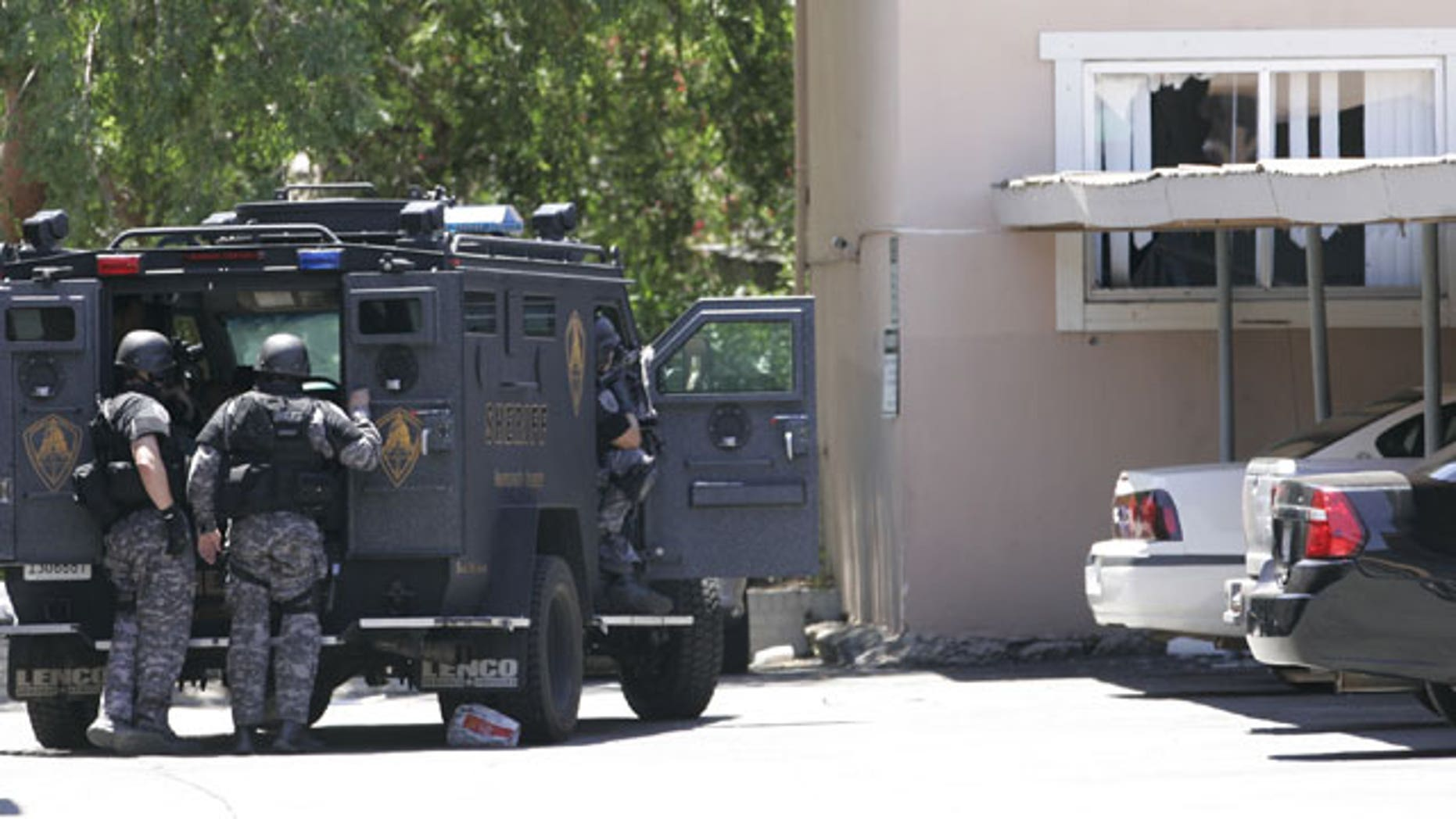June 10: Law enforcement officers huddle behind an armored vehicle outside an apartment, window at right, during a standoff where an armed robbery suspect barricaded himself and a 1-year-old boy in Sacramento, Calif.