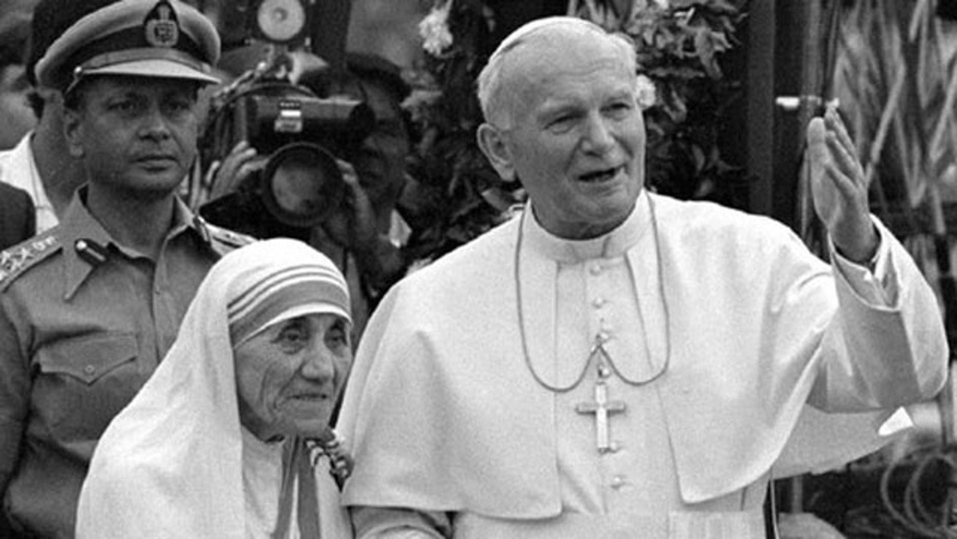 Pope John Paul II holds hands with Mother Teresa after visiting the Casa del Cuore Puro, Mother Teresa's home for the destitute and dying in the eastern Indian city of Calcutta, in this Feb. 3, 1986 file photo.