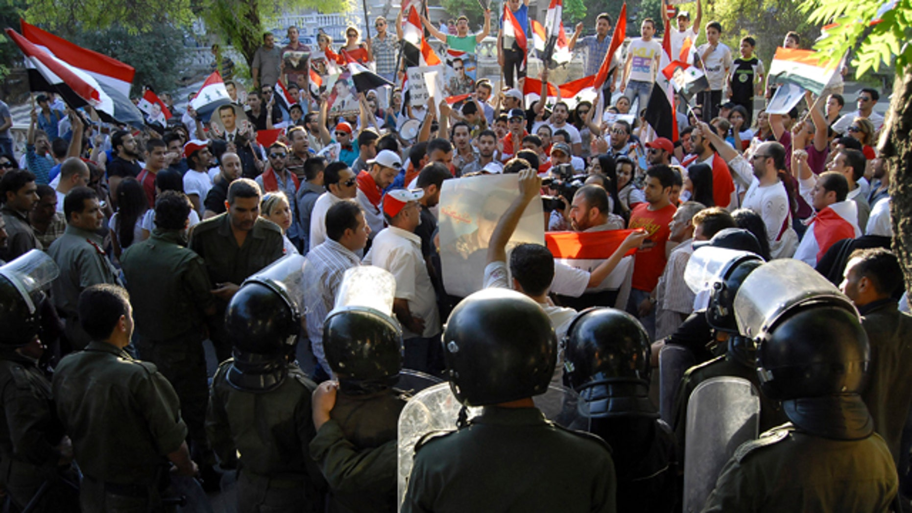 June 9: Syrian riots police officers stand guard in front of supporters of Syrian President Bashar Assad during a demonstration near the European Union office, in Damascus, Syria.