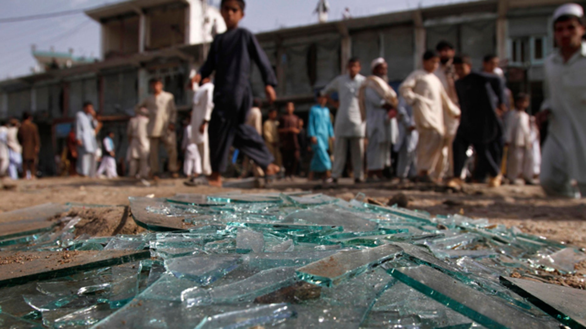 June 11: Afghans walk pass the derbis at the site of a bomb explosion in Laghman province east of Kabul, Afghanistan.