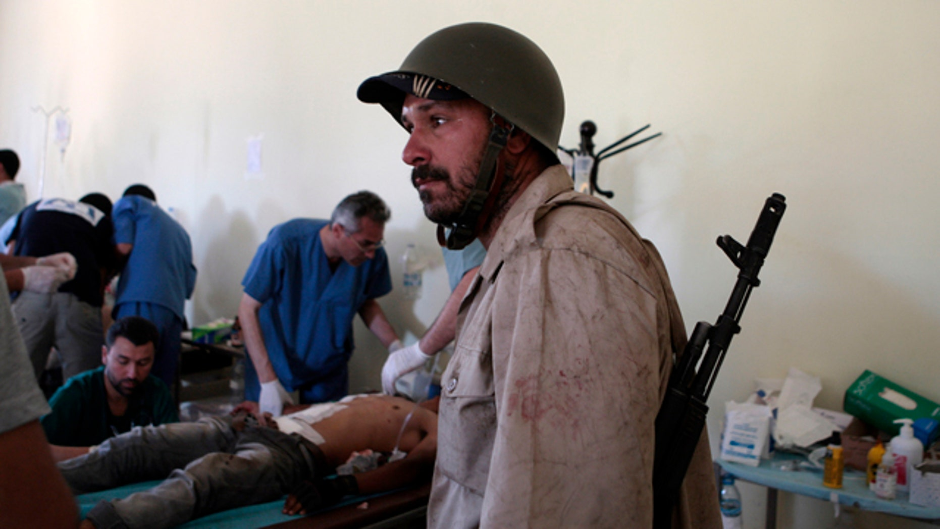 June 10: A Libyan rebel fighter arrives at a hospital as others receive treatment in Misrata, Libya.