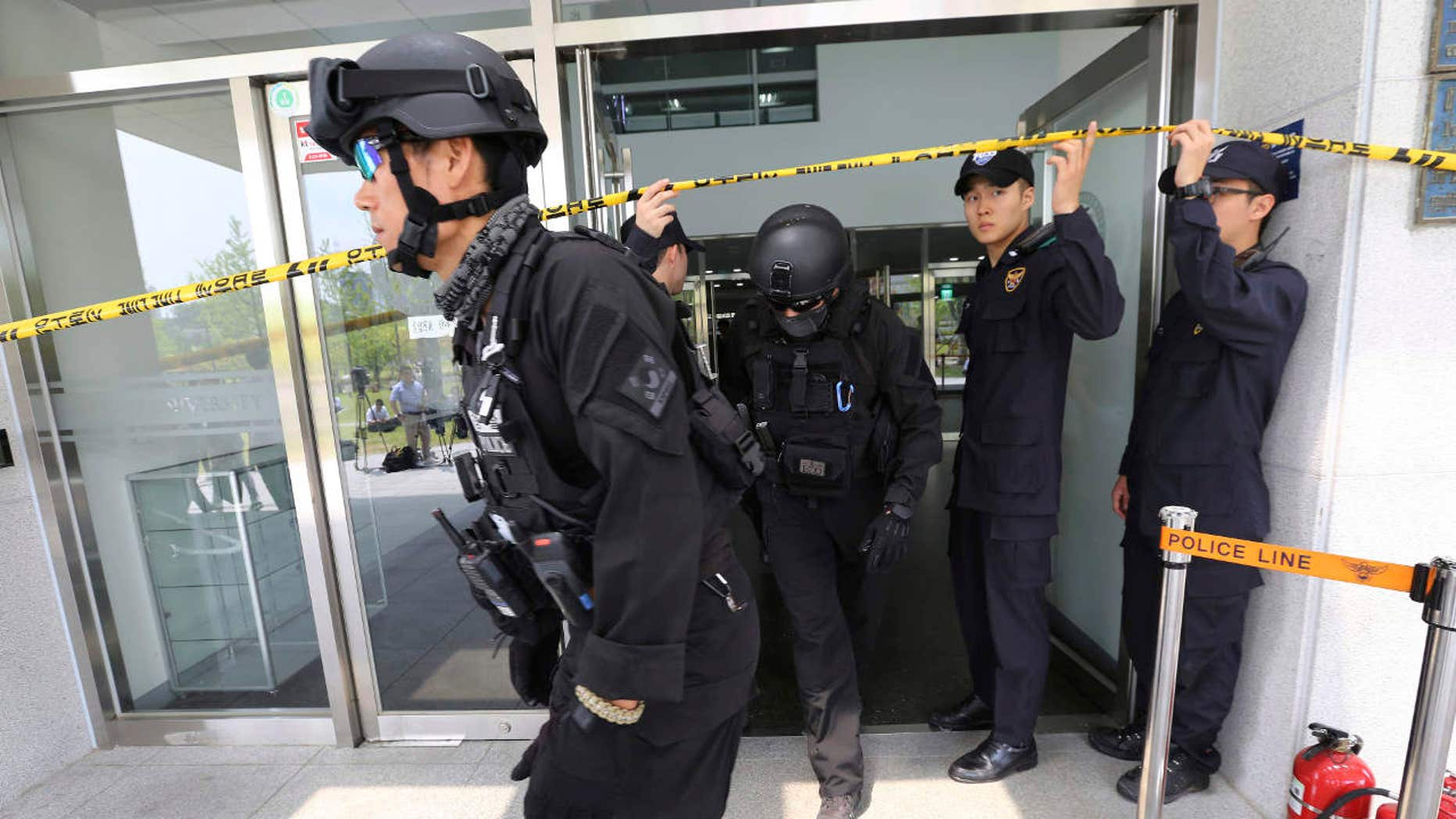 South Korean police officers come out of an engineering faculty building at Yonsei University in Seoul, South Korea, Tuesday, June 13, 2017.