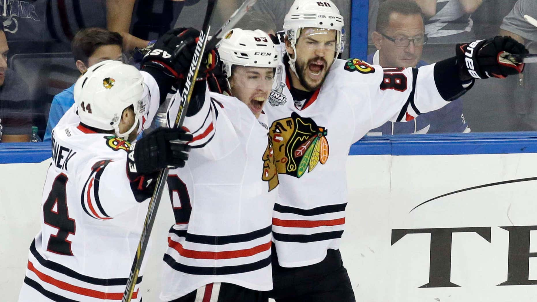 June 13, 2015: Chicago Blackhawks center Antoine Vermette (80) celebrates with left wing Teuvo Teravainen, center, and defenseman Kimmo Timonen after Vermette scored a goal against the Tampa Bay Lightning during the third period of Game 5 of the NHL hockey Stanley Cup Final.