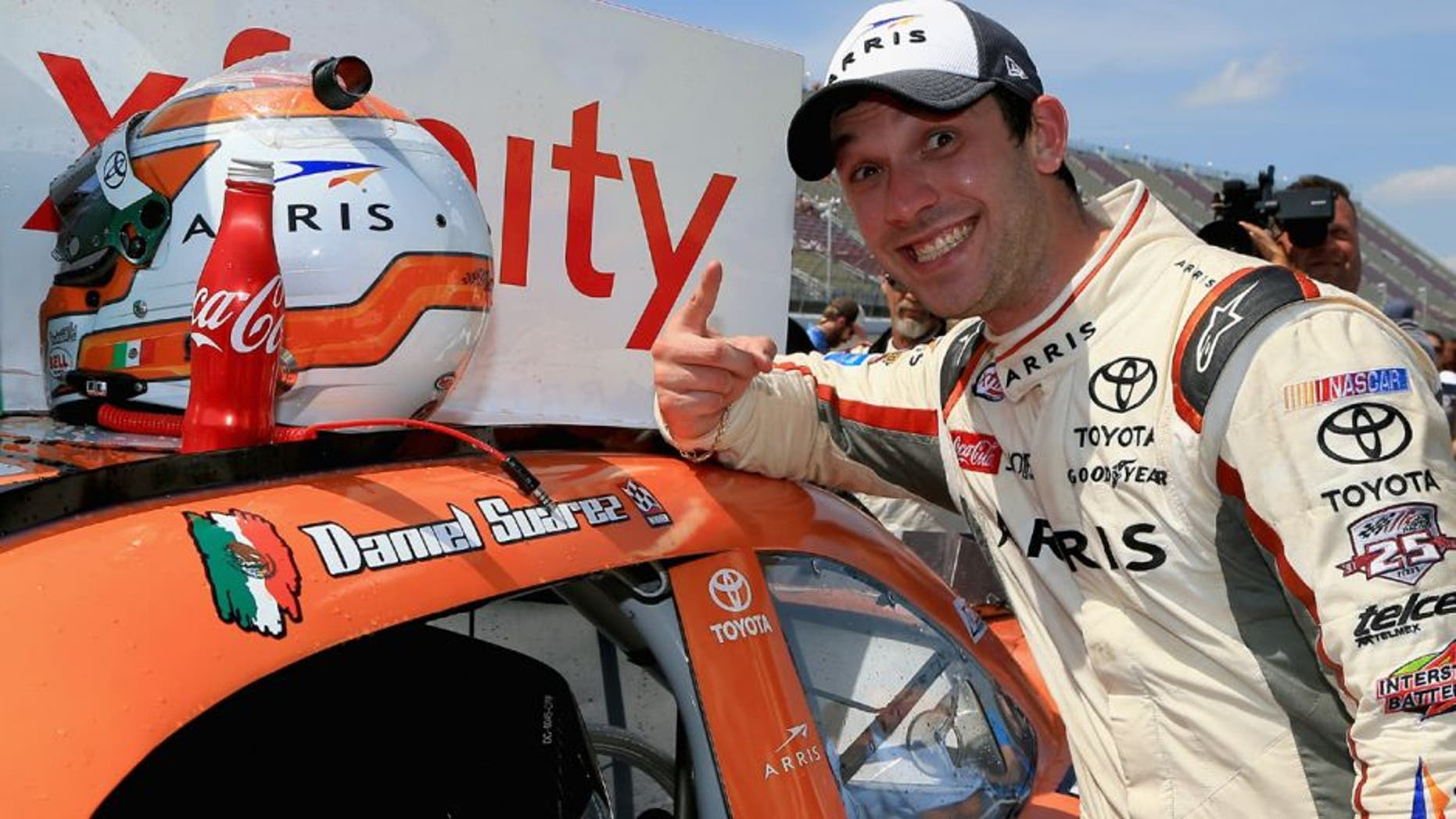 BROOKLYN, MI - JUNE 11: Daniel Suarez, driver of the #19 ARRIS Toyota, places a winner's sticker decal on his car after winning the NASCAR XFINITY Series Menards 250 at Michigan International Speedway on June 11, 2016 in Brooklyn, Michigan. (Photo by Daniel Shirey/NASCAR via Getty Images)