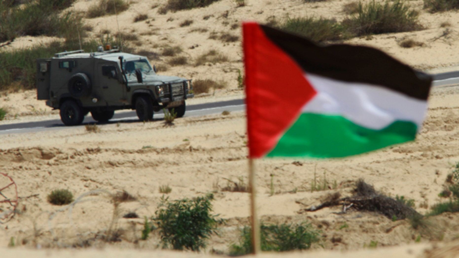 June 15: Israeli soldiers in a jeep patrol near the Gaza border as a Palestinian national flag set up by protesters waves in the foreground.