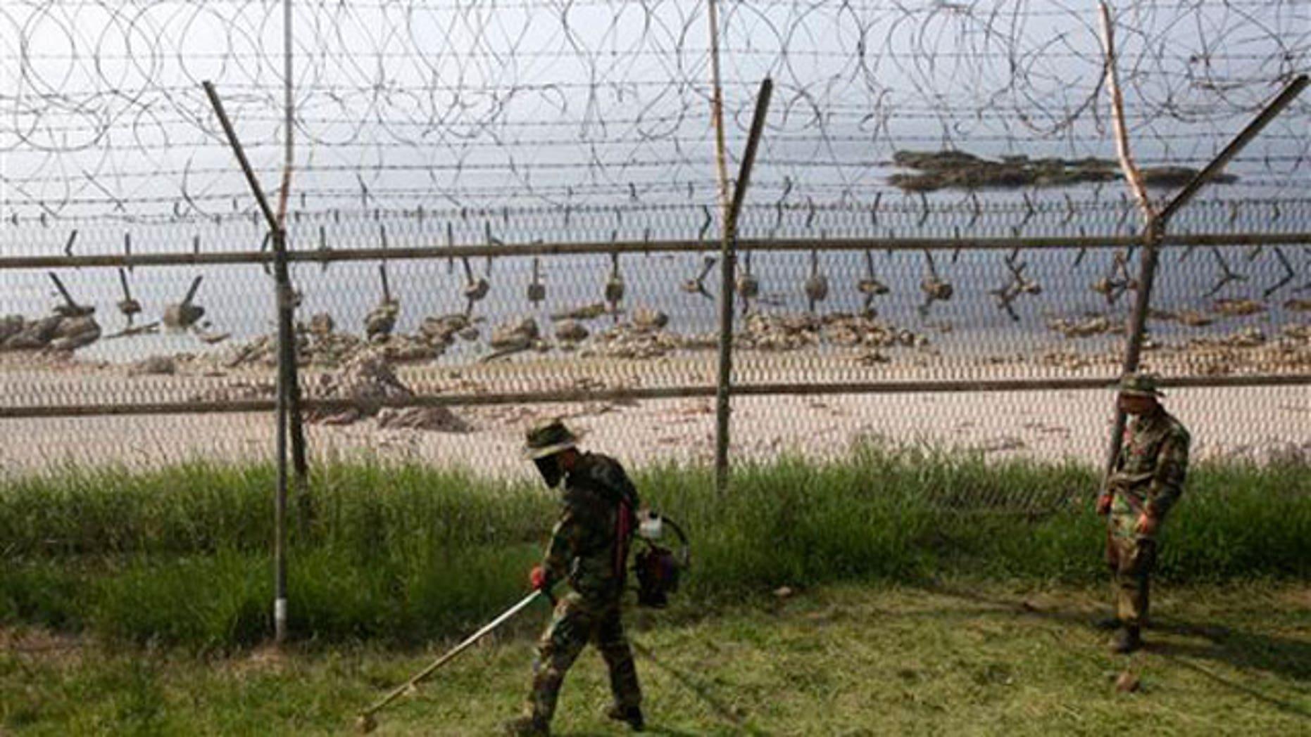 June 15: South Korean Marines work along the fence on Baengnyeong Island, South Korea, near the border with North Korea.