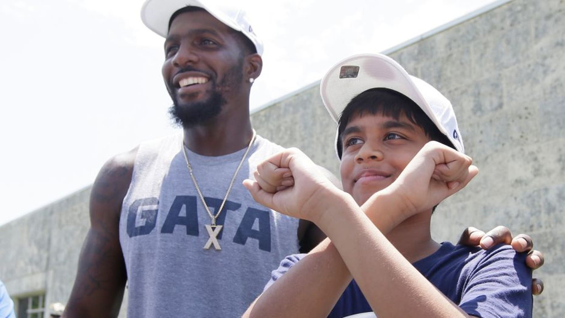 Dallas Cowboys wide receiver Dez Bryant, left, stands by as 11-year-old spelling bee champion Nahir Janga of Austin, throws up a celebratory 'X' at the NFL football team's minicamp at Valley Ranch in Irving, Texas, Wednesday, June 15, 2016. Janga was on hand to visit with the Cowboys and meet Bryant who inspired him to throw up an 'X' when he won the spelling bee. (AP Photo/LM Otero)